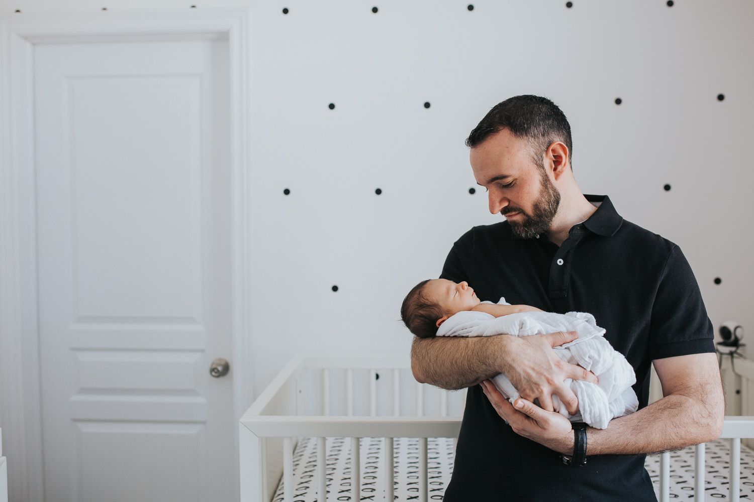 new dad holding and looking at sleeping 2 week old baby boy in nursery - Markham lifestyle photos
