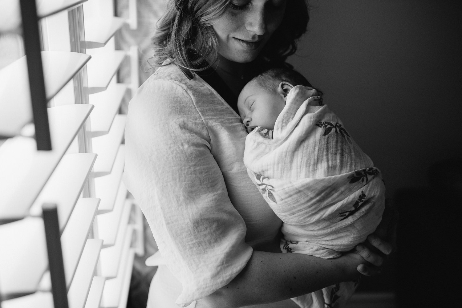 new mother snuggles sleeping, swaddled 2 week old baby daughter to chest - Newmarket Lifestyle Photography