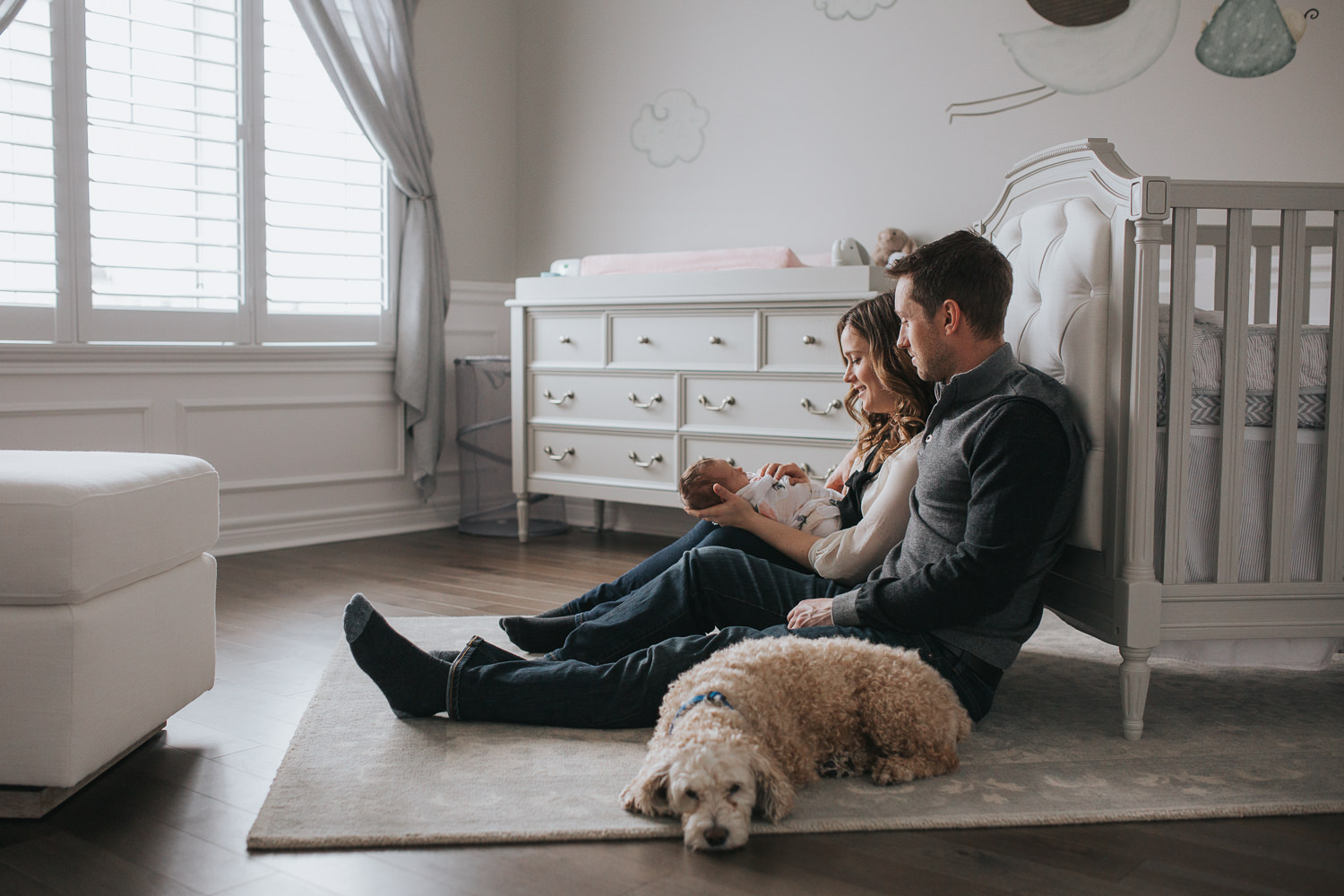 first time parents sitting on nursery floor holding 2 week old baby daughter, family dog looking on - Stouffville Lifestyle Photos