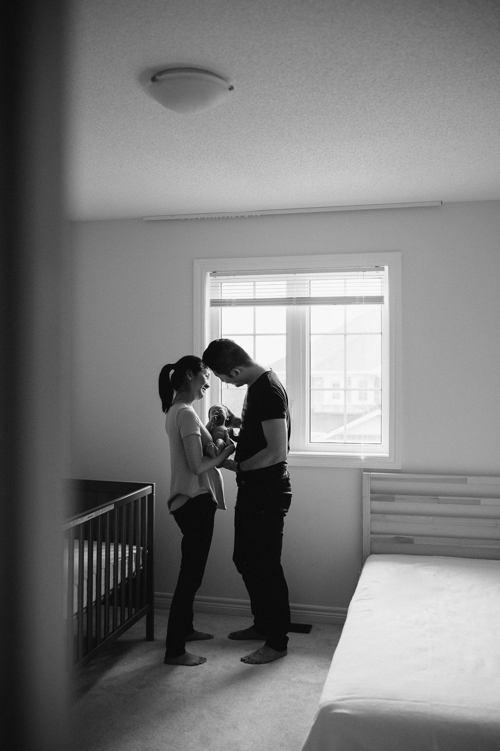 new parents hold 2 week old baby son, mom looking up at dad -Barrie In-Home Photos