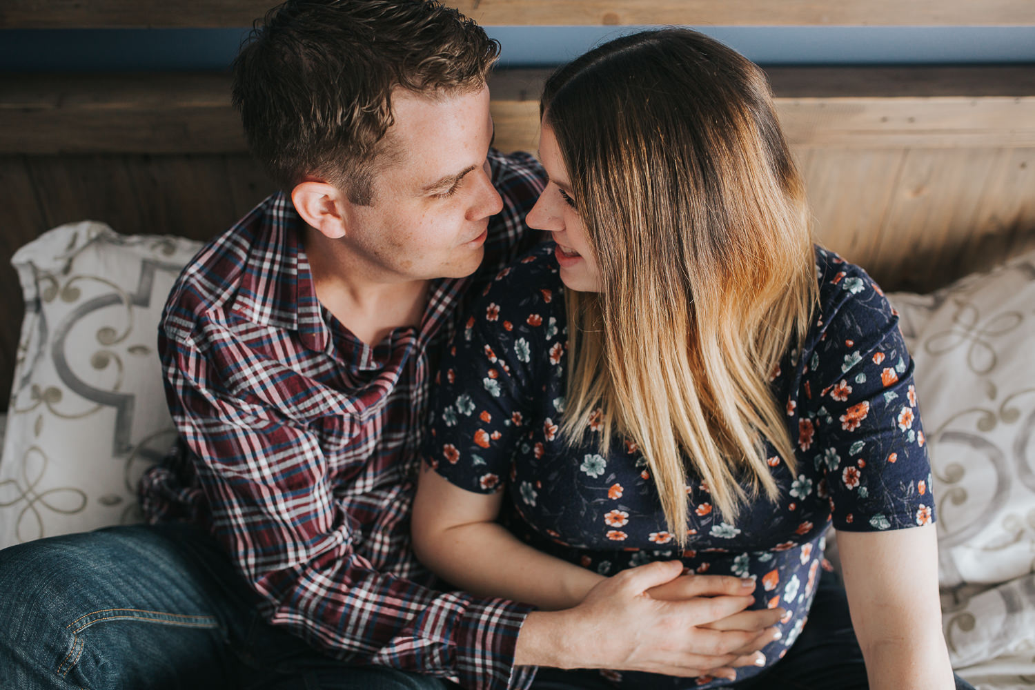expecting couple snuggles on bed, hands holding wife's pregnant belly - Stouffville In-Home Photography