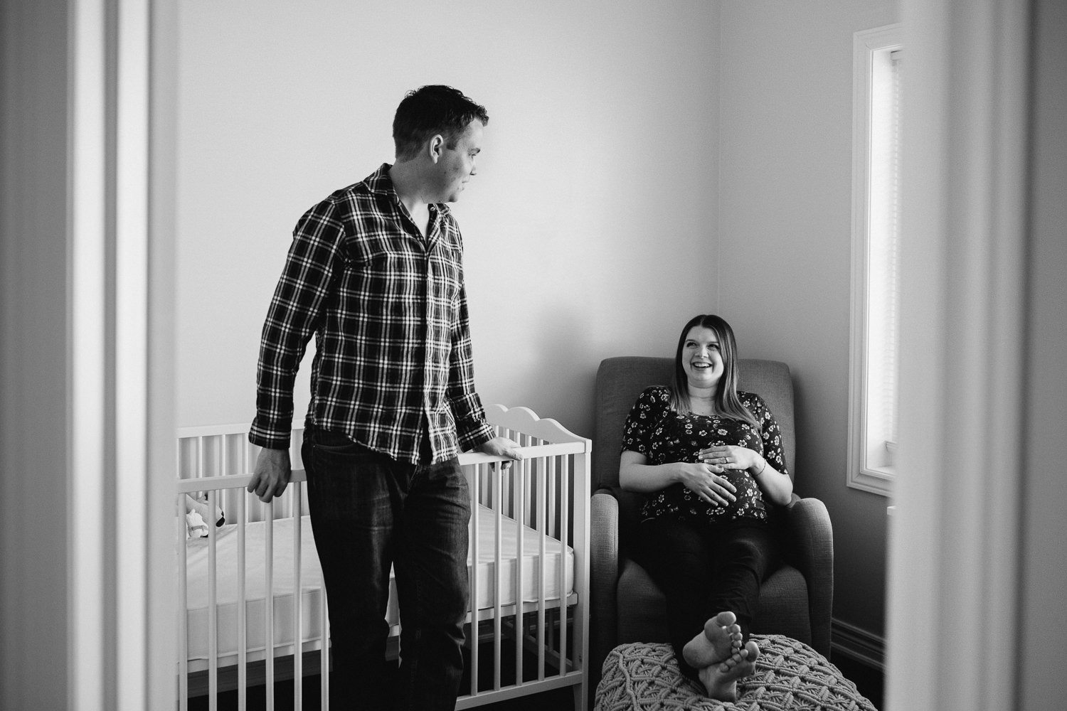 pregnant mom sits in nursery glider smiling at husband, hands on baby belly - Uxbridge In-Home Photography