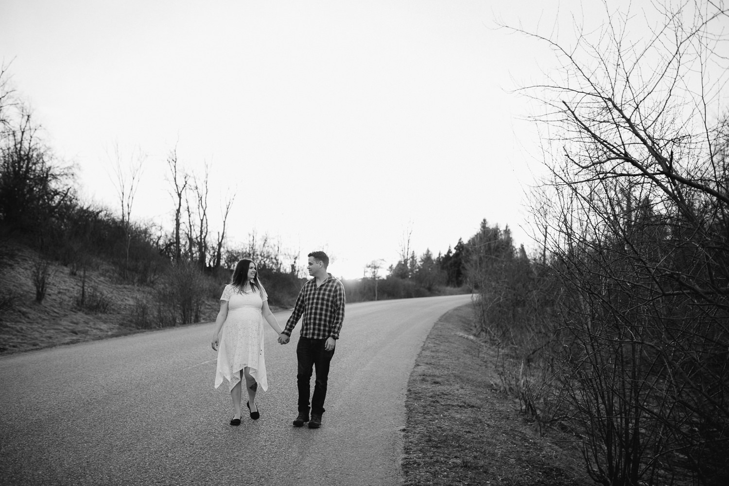husband and pregnant wife walk down road holding hands - Newmarket Lifestyle Photos