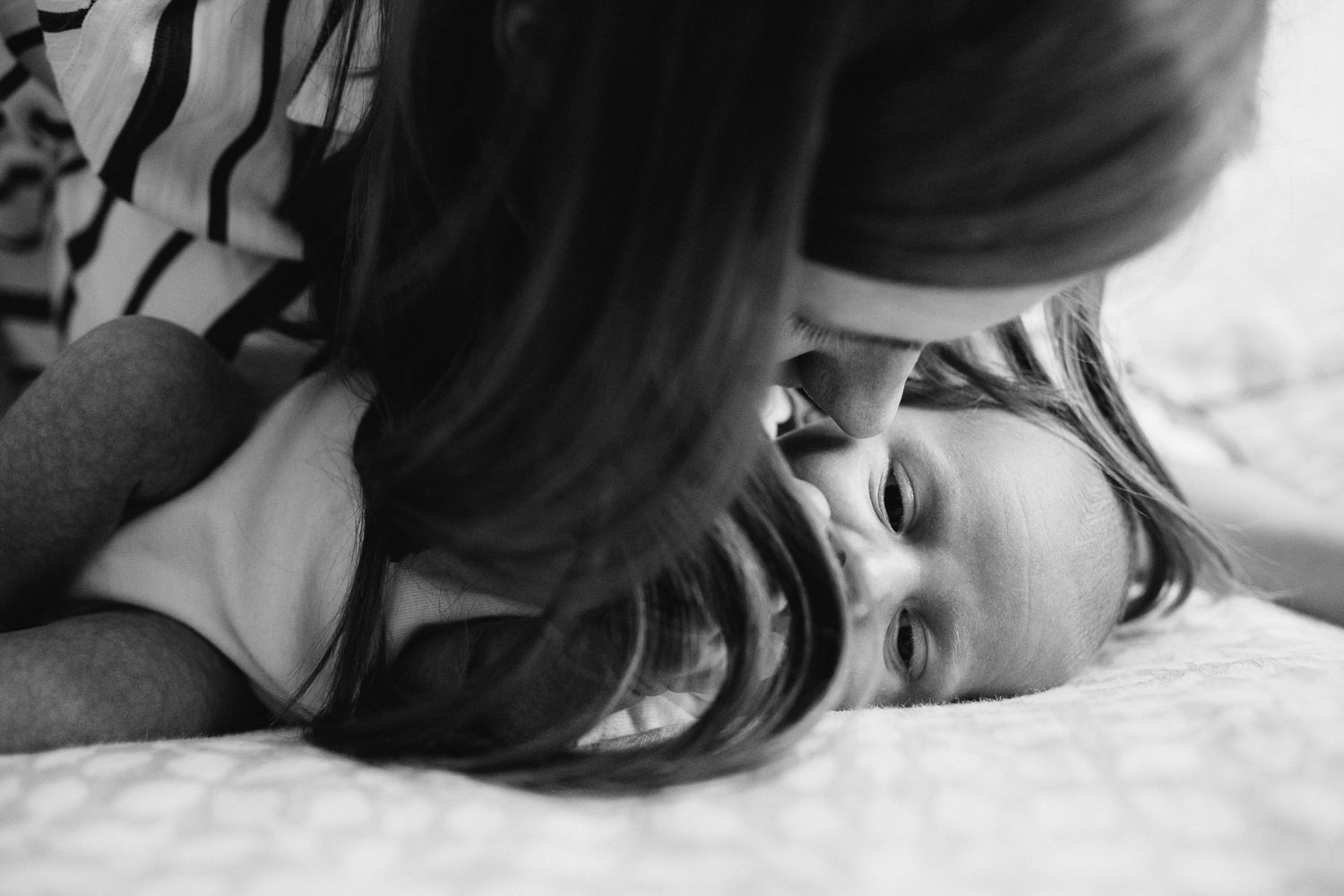 first time mother kisses 2 week old baby son's forehead as he lies on bed - Markham Lifestyle Photography