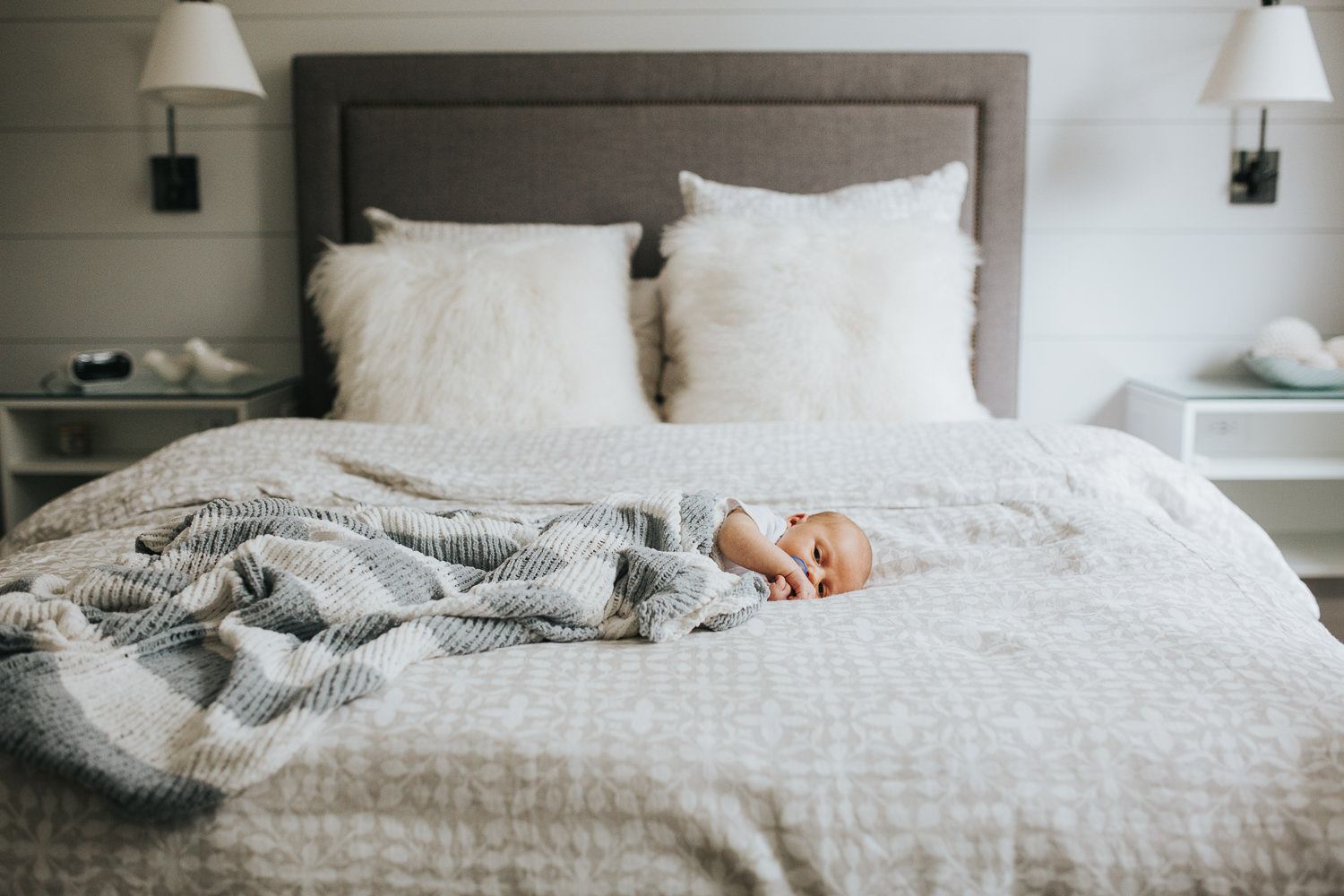 two week old baby boy lying on bed under hand knitted blanket - Newmarket In-Home Photography