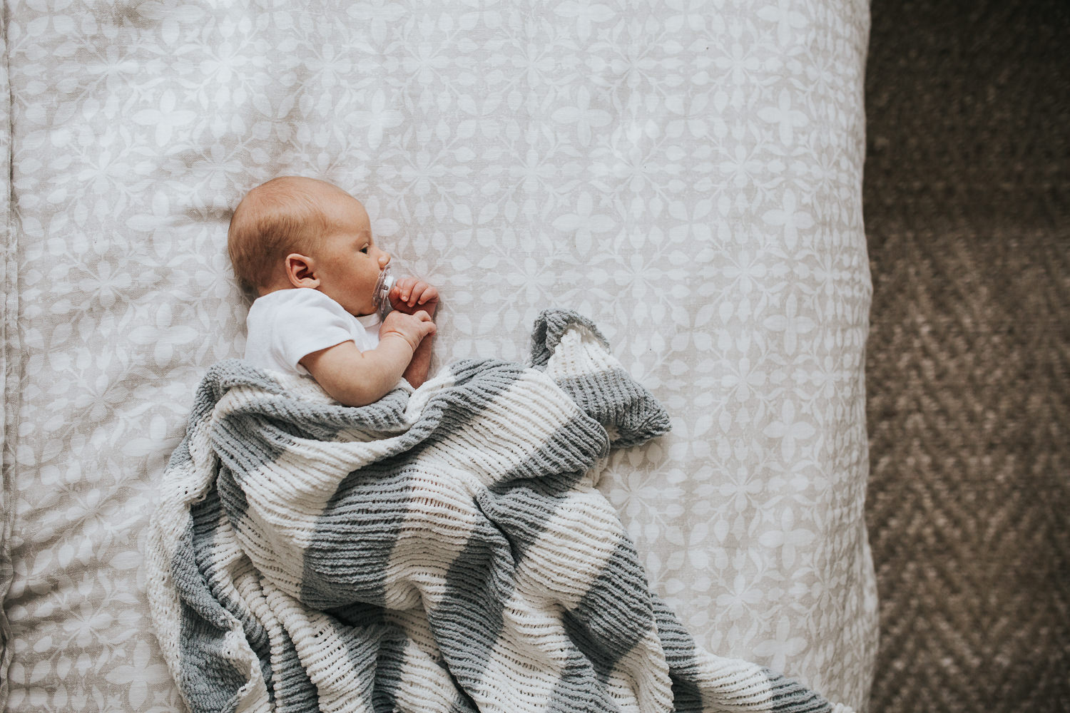 two week old baby boy lying on bed under hand knitted blanket - Stouffville In-Home Photography