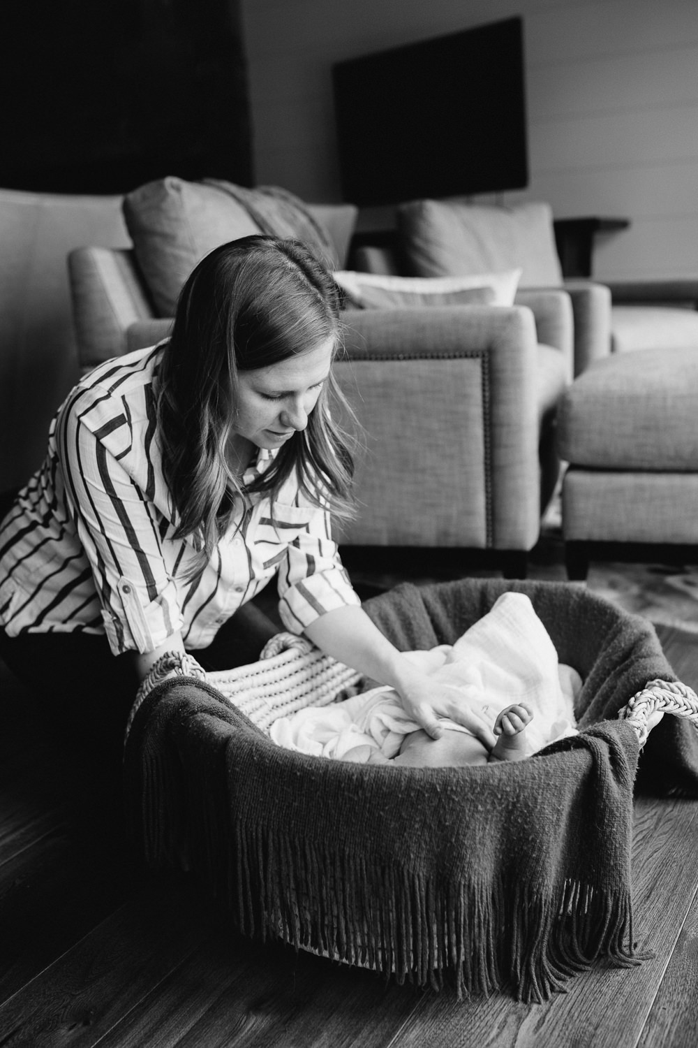 new mom looks at 2 week old baby son lying in Moses basket - Uxbridge In-Home Photos