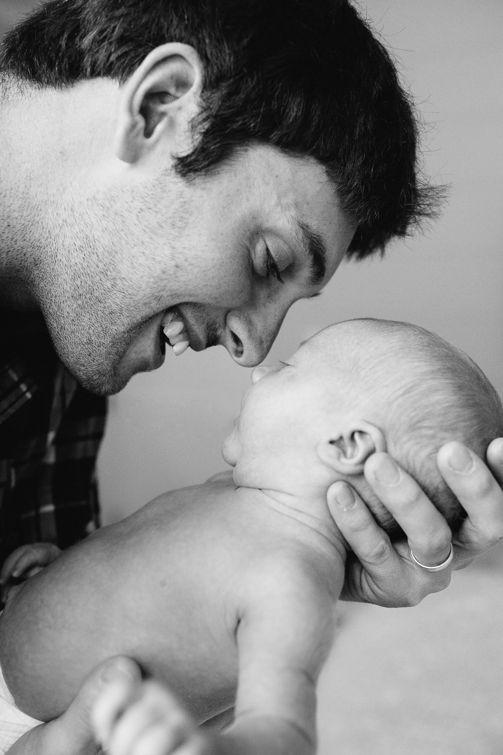 new dad smiling and touching noses with 2 week old baby son - Newmarket Lifestyle Photography