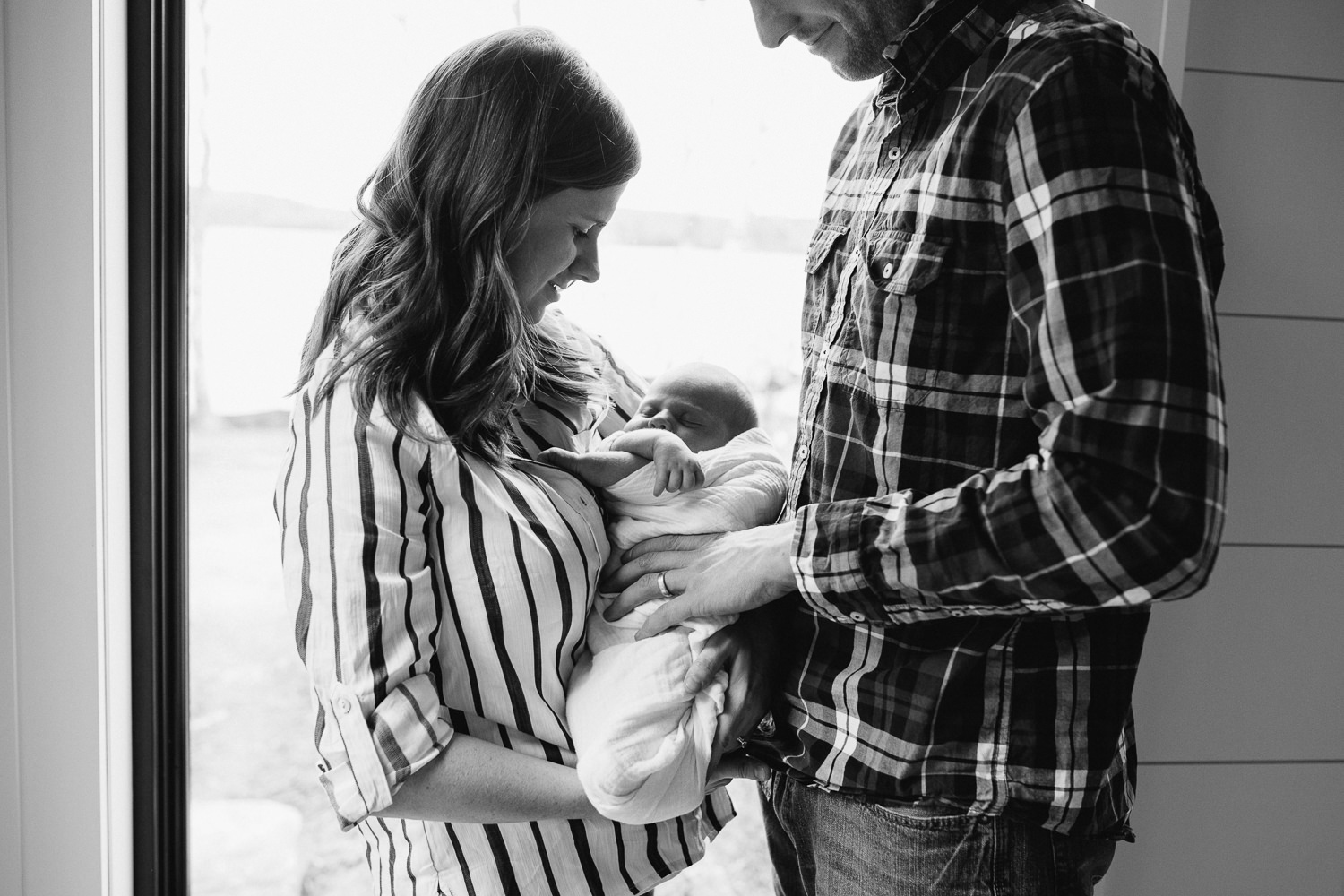 first time parents standing holding and looking at 2 week old baby son - Stouffville Lifestyle Photos