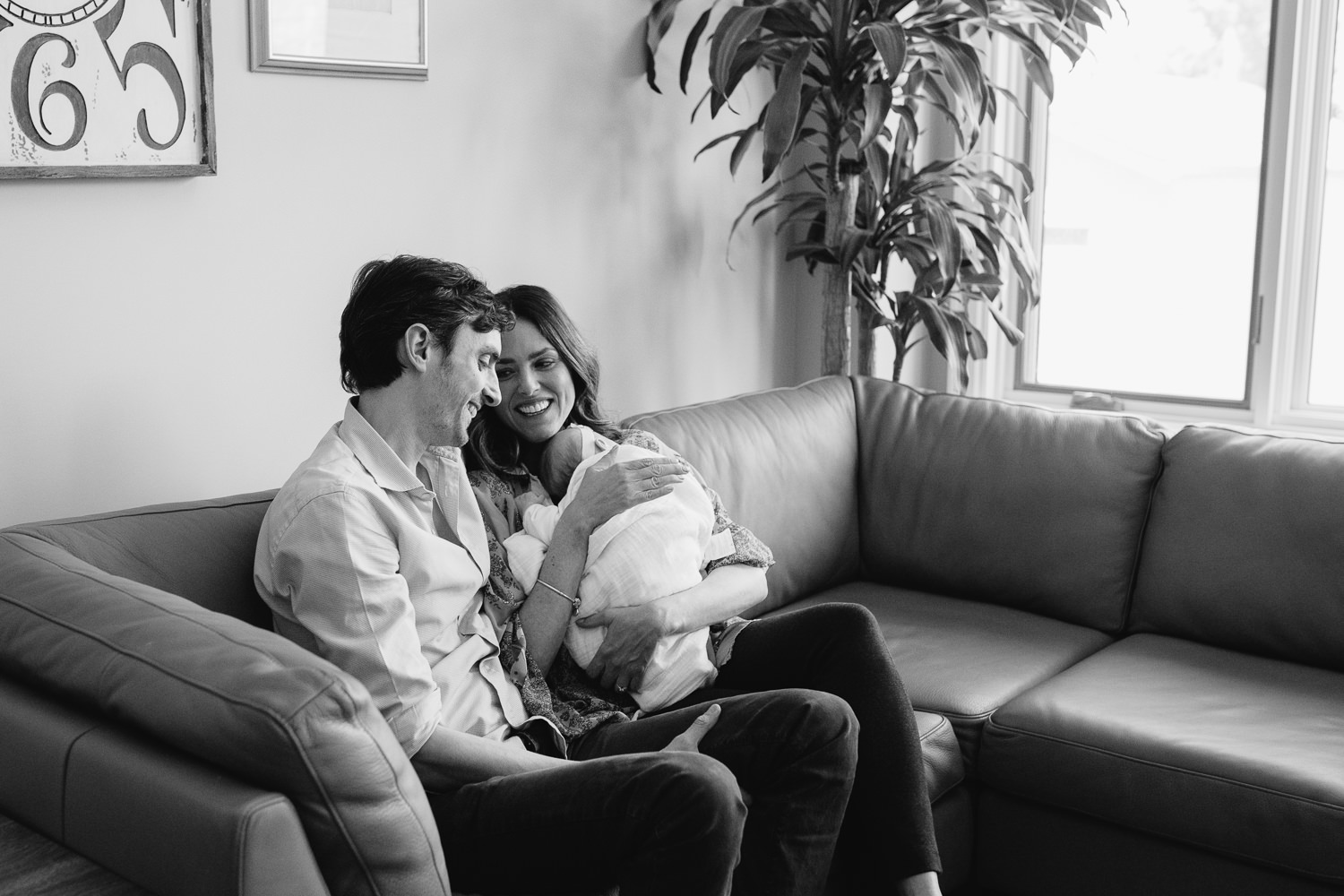 new parents sitting on couch holding 2 month old baby daughter, laughing - Newmarket In-Home Photography