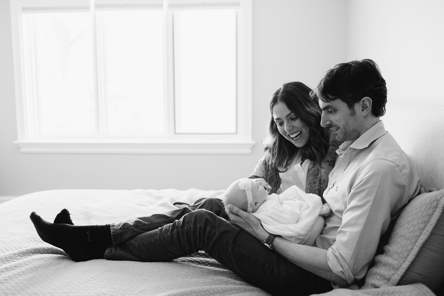 husband and wife sitting on master bed, dad holding 2 month old baby girl - Markham In-Home Photography