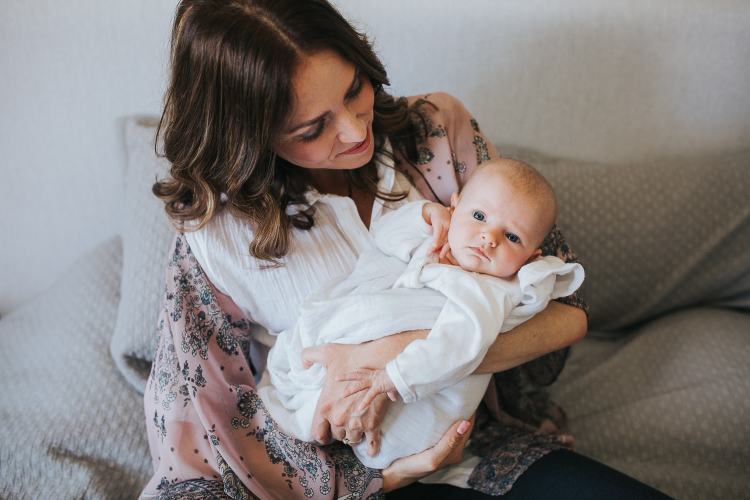 new mom sitting on bed holding 2 month old baby girl, who is looking at camera - Stouffville In-Home Photos