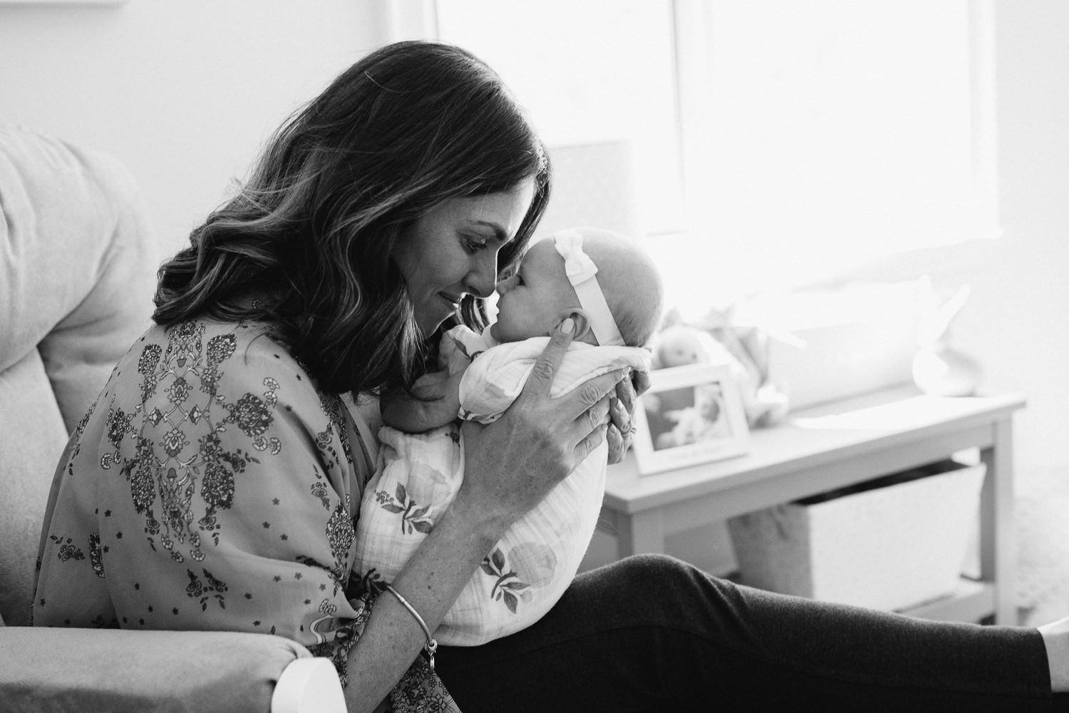 new mom sitting in nursery glider giving 2 month old baby girl Eskimo kiss - Barrie Lifestyle Photos