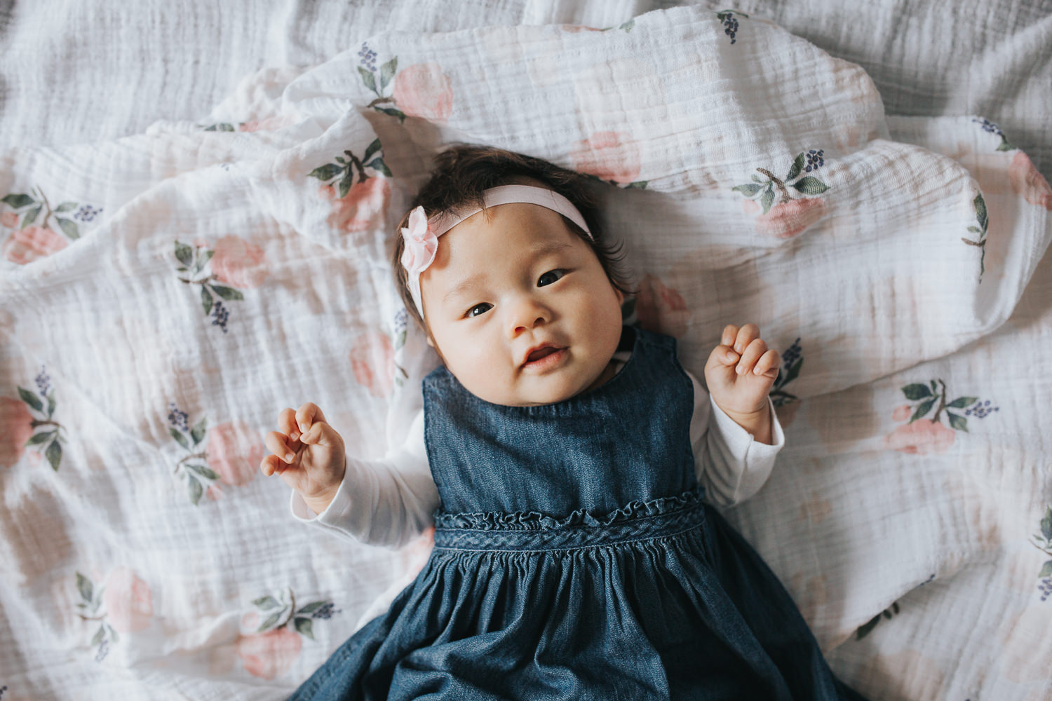 3 month old baby girl in blue dress lying on floral blanket looking at camera -Newmarket Lifestyle Photography
