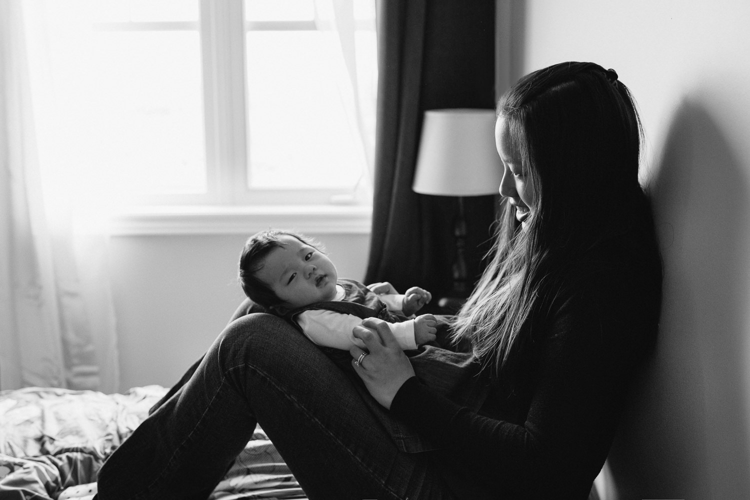 3 month old baby girl lying on mom's legs on master bed, mother looking at daughter - Markham Lifestyle Photos