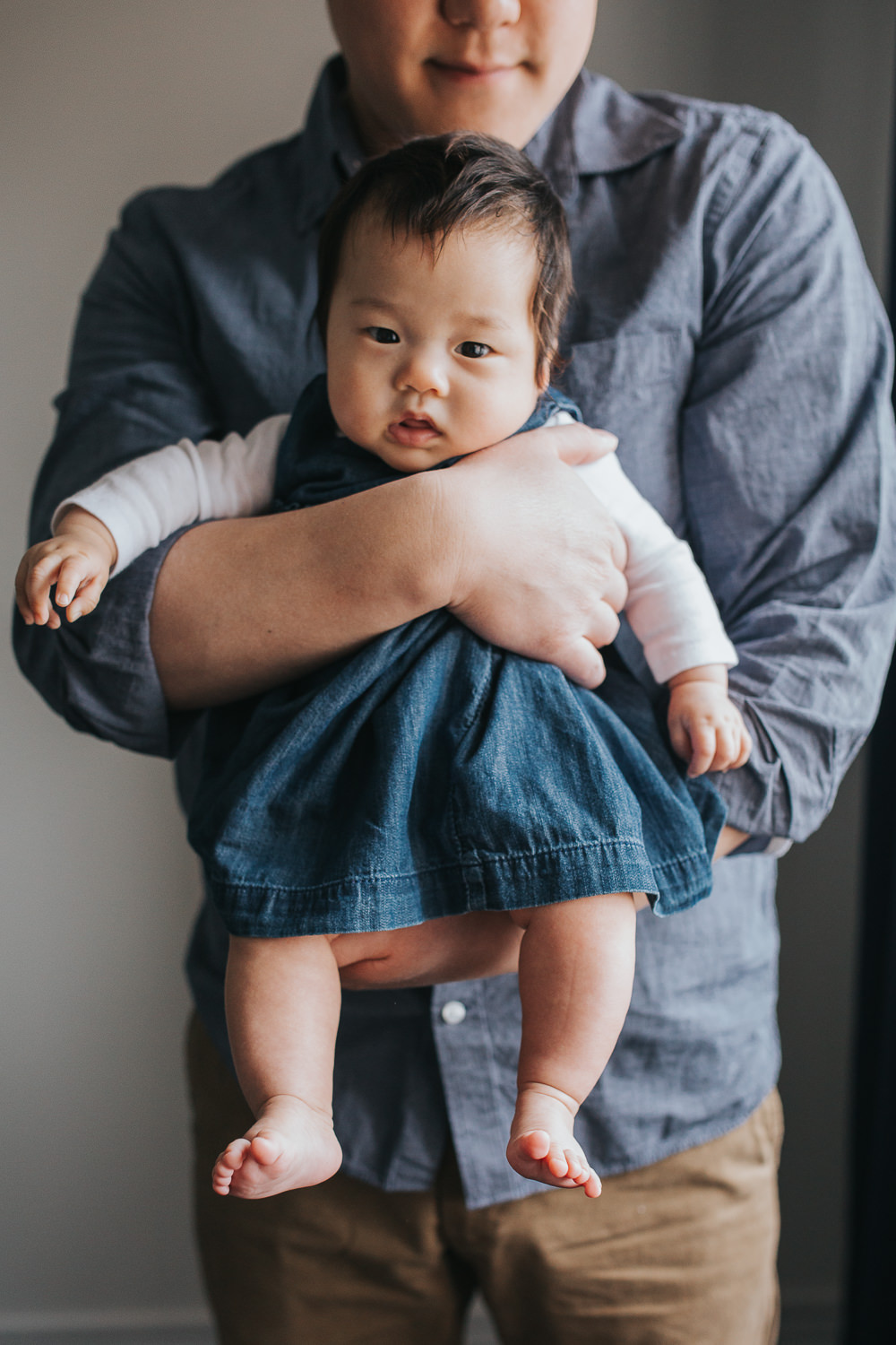 3 month old baby girl in blue dress sits in dad's arms, looking at camera - Barrie In-Home Photos