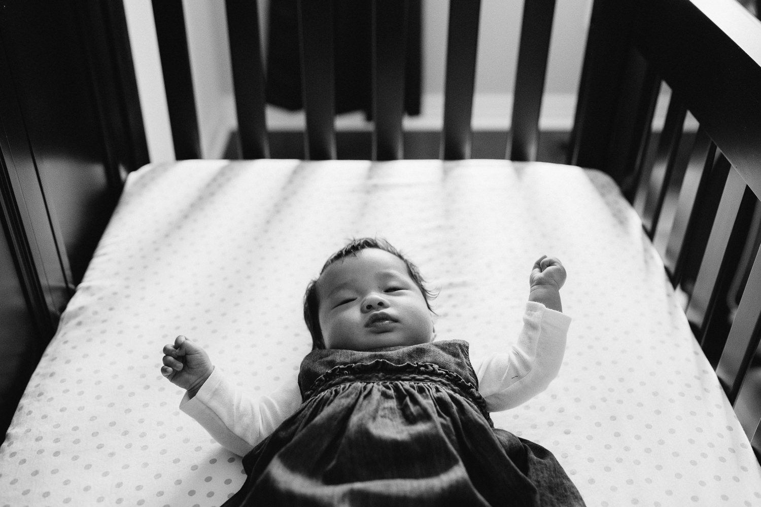 3 month old baby girl in blue dress lying in nursery crib, looking at camera - Barrie Lifestyle Photography