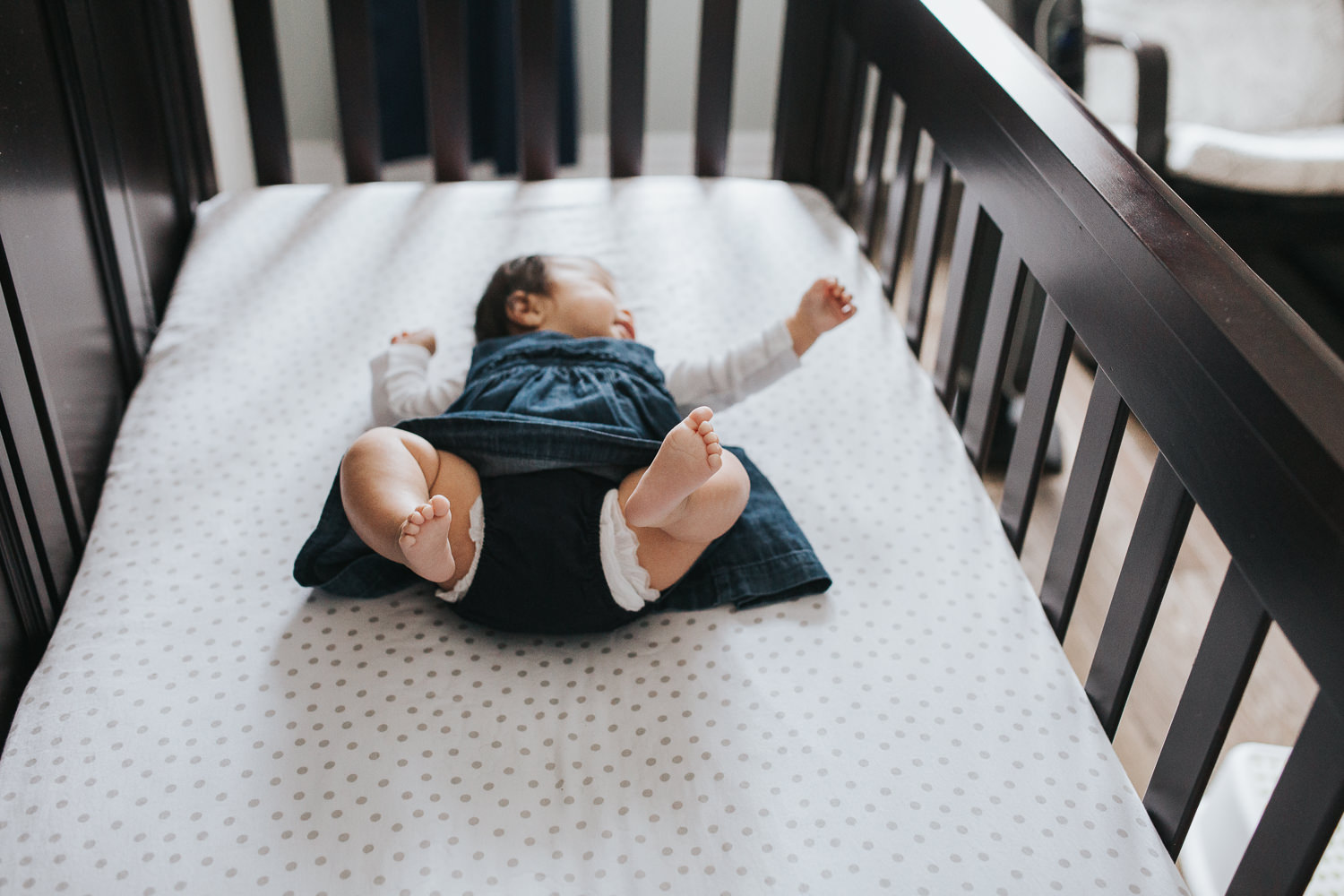 3 month old baby girl in blue dress lying in nursery crib with feet in air - Uxbridge Lifestyle Photography