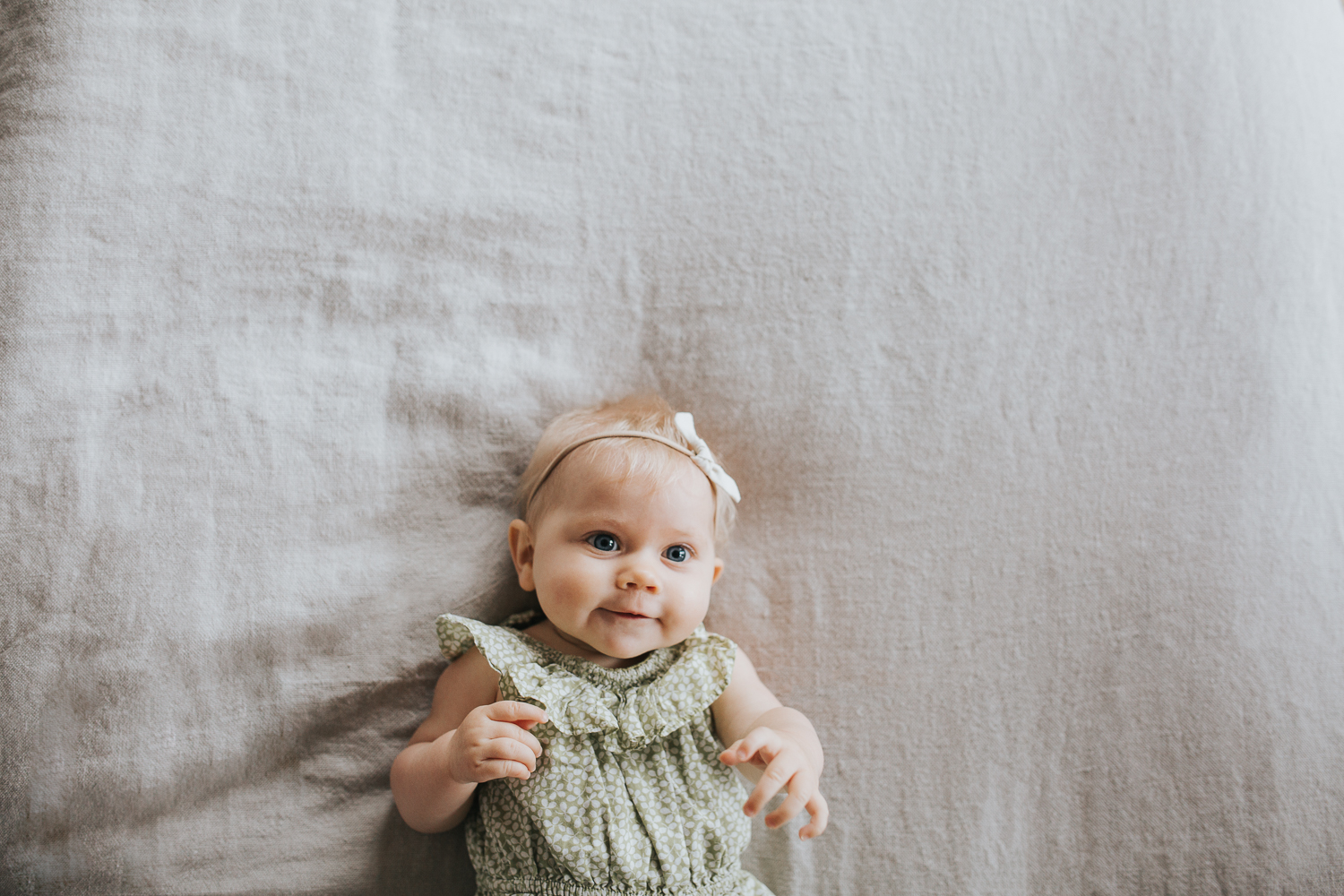 6 month old baby girl with blonde hair and blue eyes lying on bed - Newmarket Family Lifestyle Photography