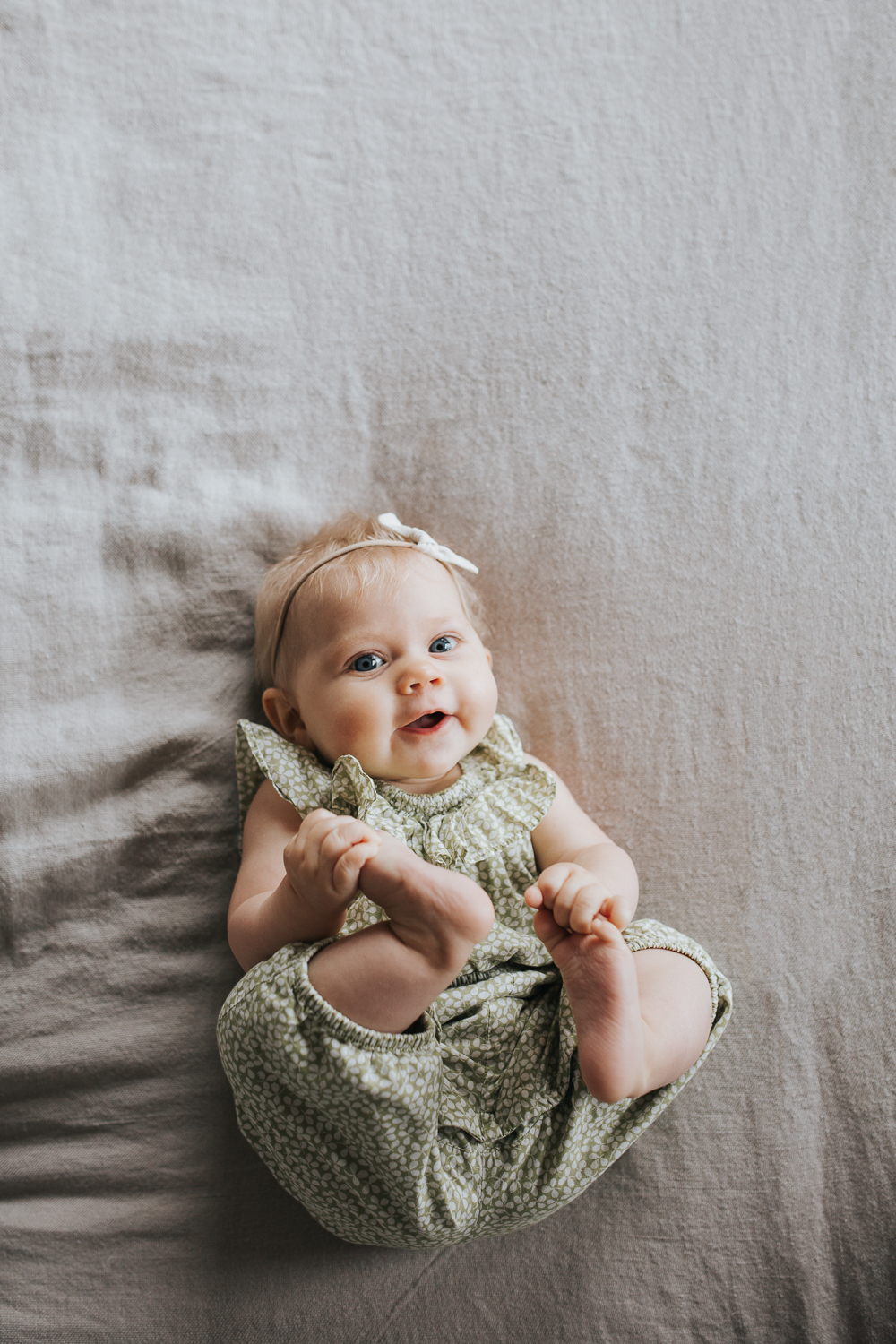 6 month old baby girl with blonde hair and blue eyes lying on bed holding feet -Markham Family Lifestyle Photography