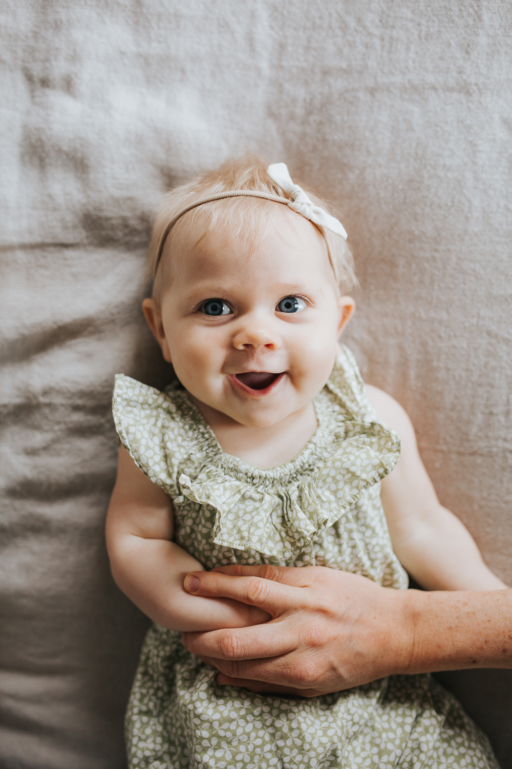 6 month old baby girl with blonde hair and blue eyes lying on bed smiling -Barrie Family Lifestyle Photography