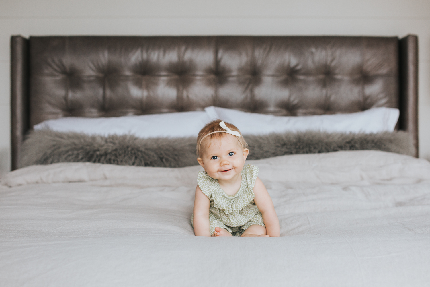 6 month old baby girl with blonde hair and blue eyes sitting on bed smiling at camera - Barrie In-home Family Photography