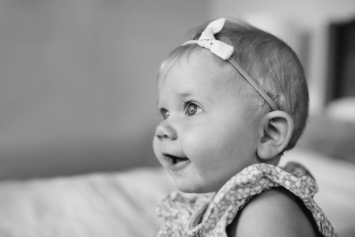 6 month old baby girl with blonde hair and blue eyes sitting on bed - Newmarket In-home Family Photos