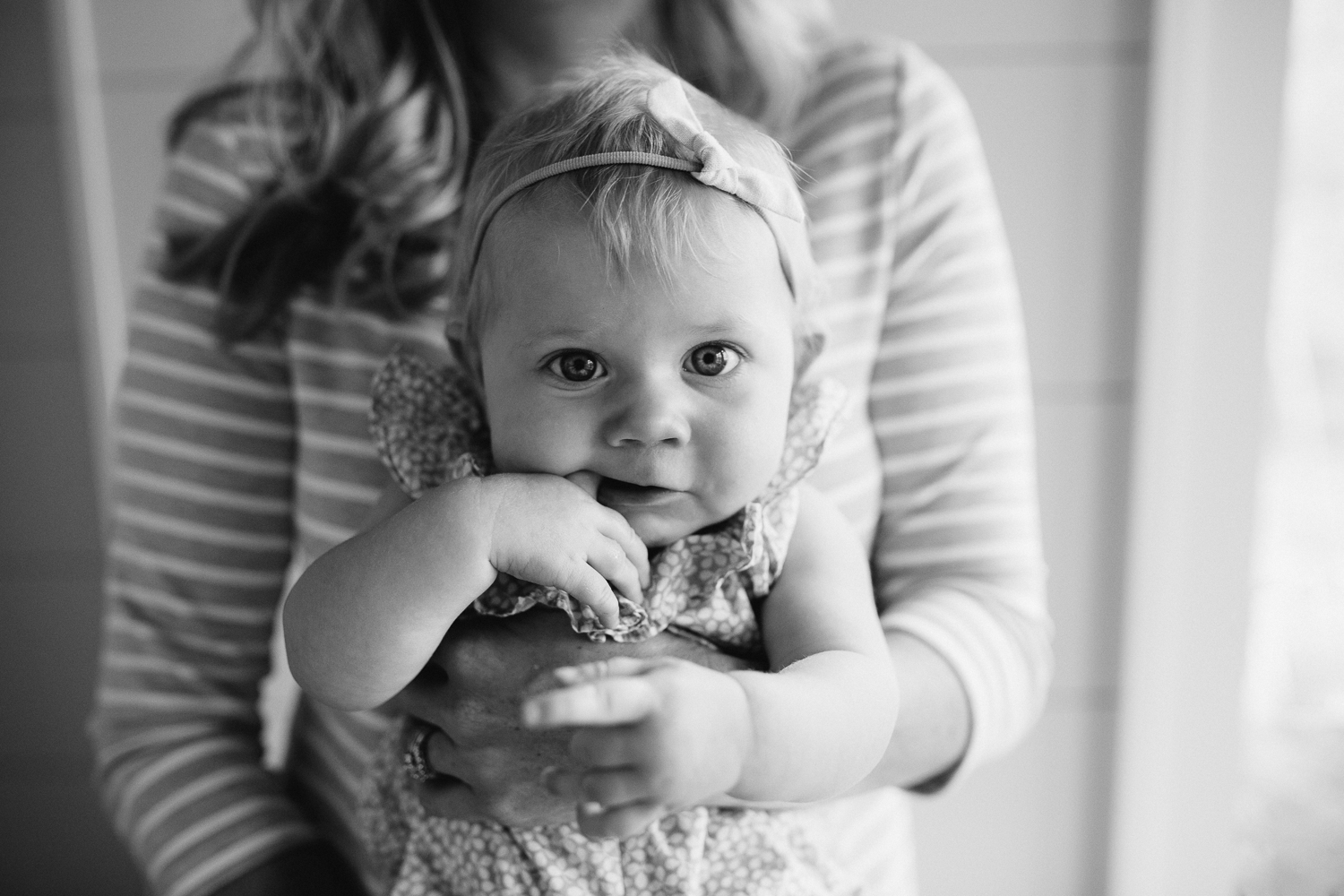 6 month old baby girl with blonde hair and blue eyes in mom's arms chewing on finger and looking at camera - Barrie In-home Family Photos