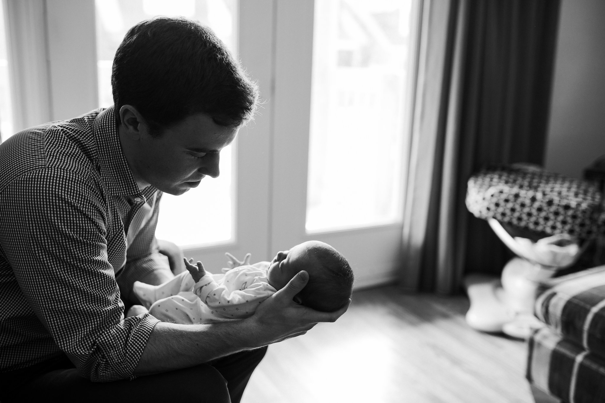 first time dad sitting in chair holding and looking at 4 week old baby girl in sleeper - Stouffville In-Home Photography