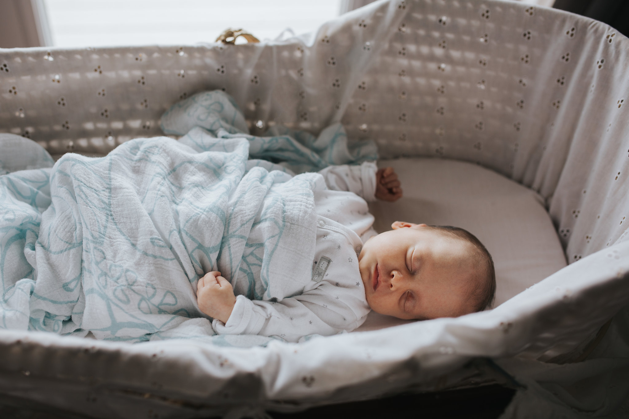 4 week old baby girl sleeping in Moses basket wearing a sleeper and covered in swaddle - Barrie In-Home Photos