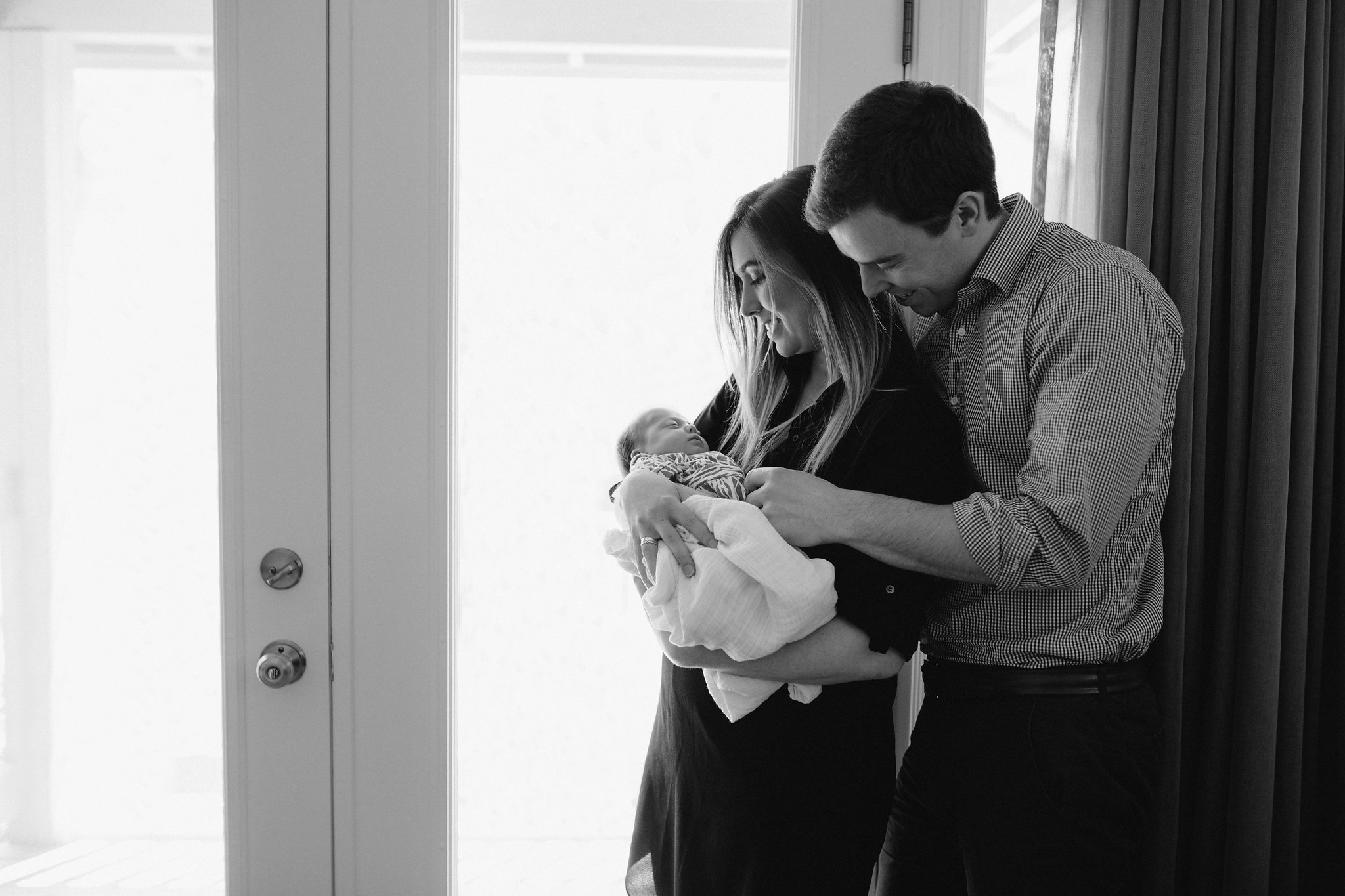 new parents standing at window holding and looking at 4 week old baby girl - Markham Lifestyle Photos