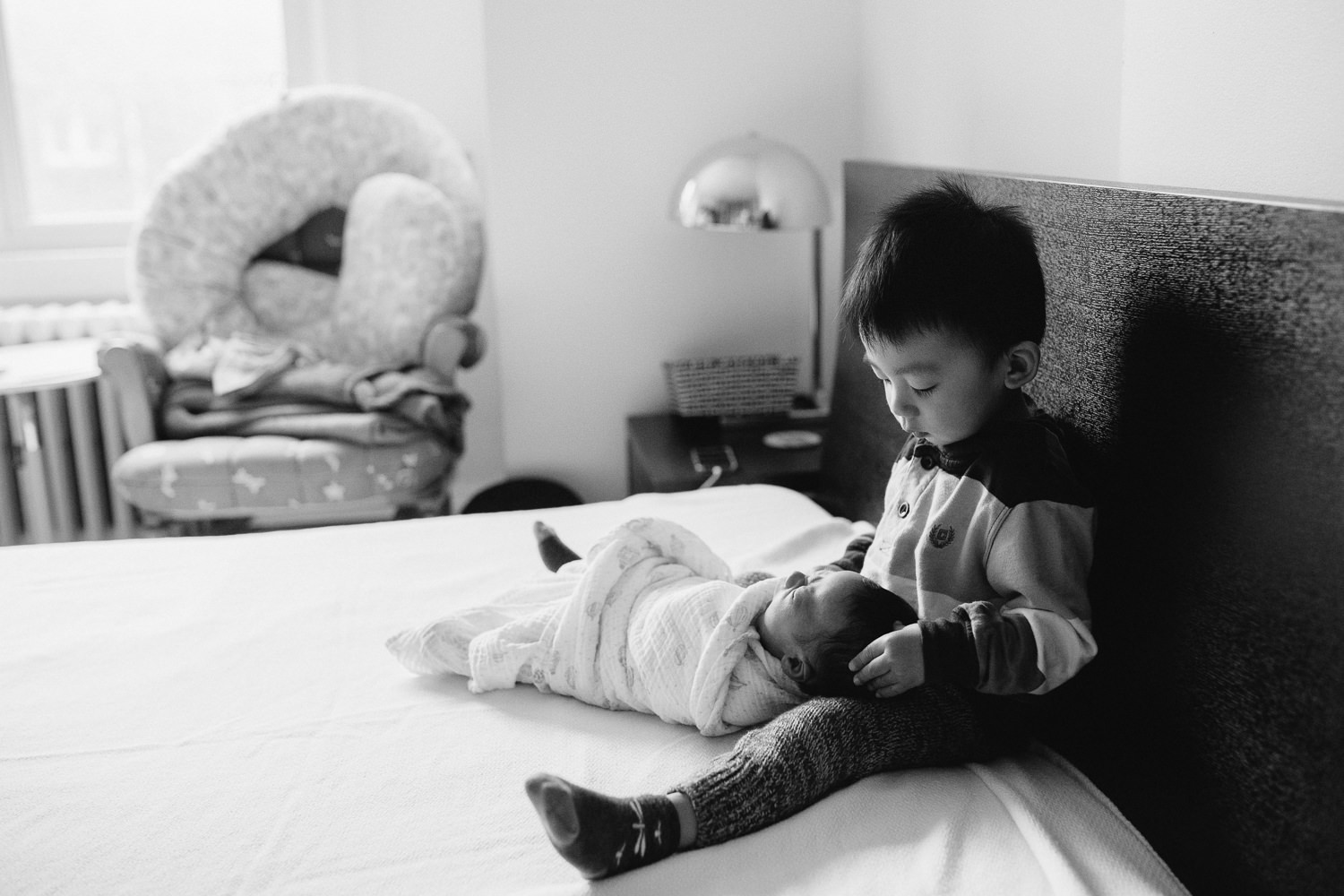 2 year old toddler boy sitting on bed holding 2 week old baby brother - Barrie In-Home Photography