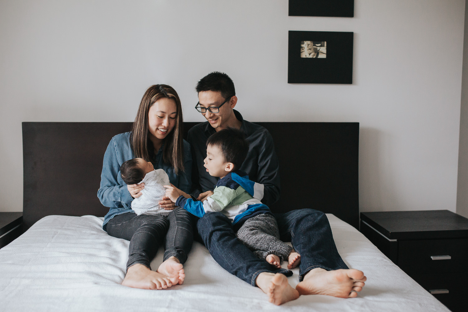 Family of 4 with 2 year old toddler boy and 2 week old baby son sitting on bed - Newmarket In-Home Photos