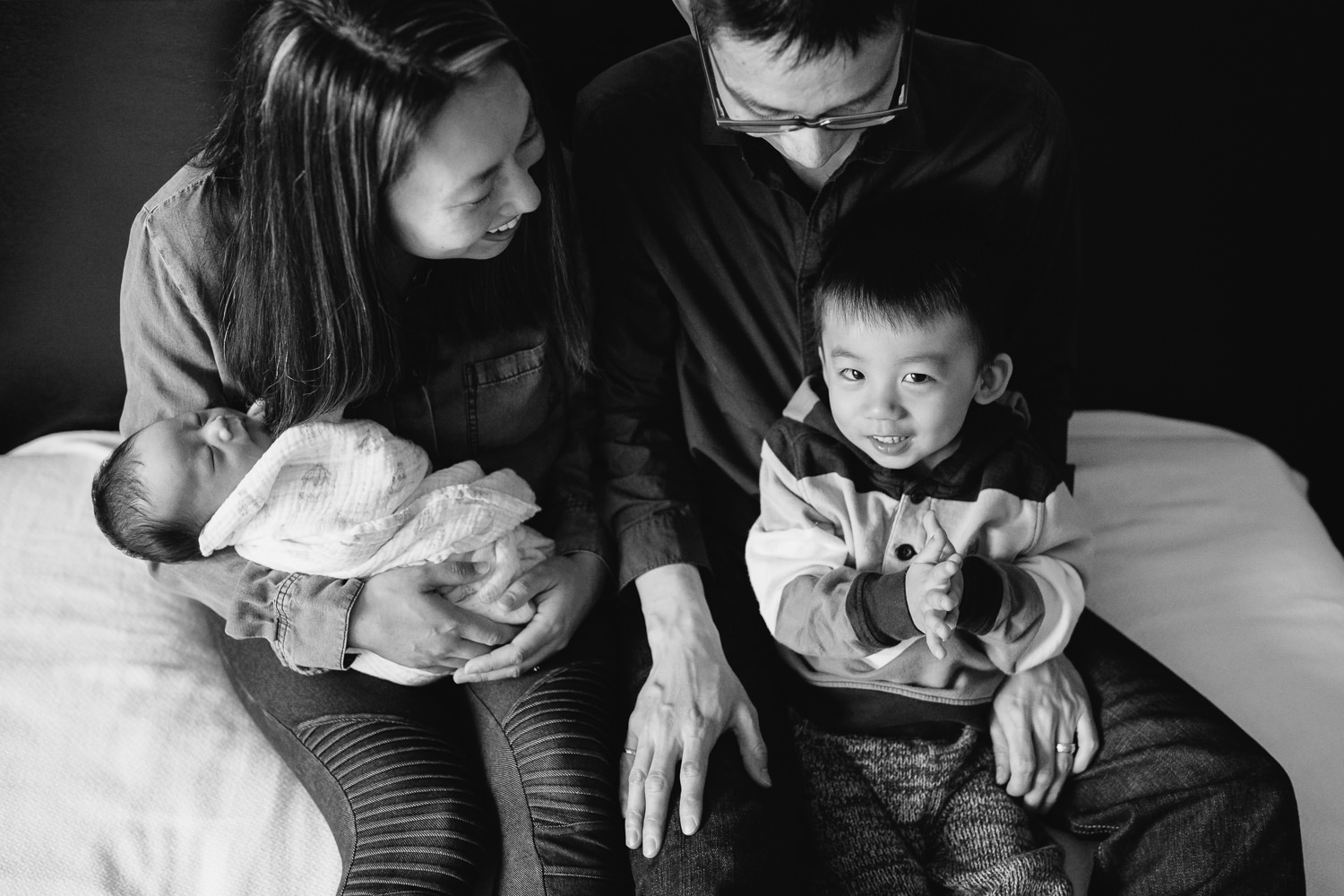 Family of 4 with 2 year old toddler boy and 2 week old baby son sitting on bed - Stouffville In-Home Photos