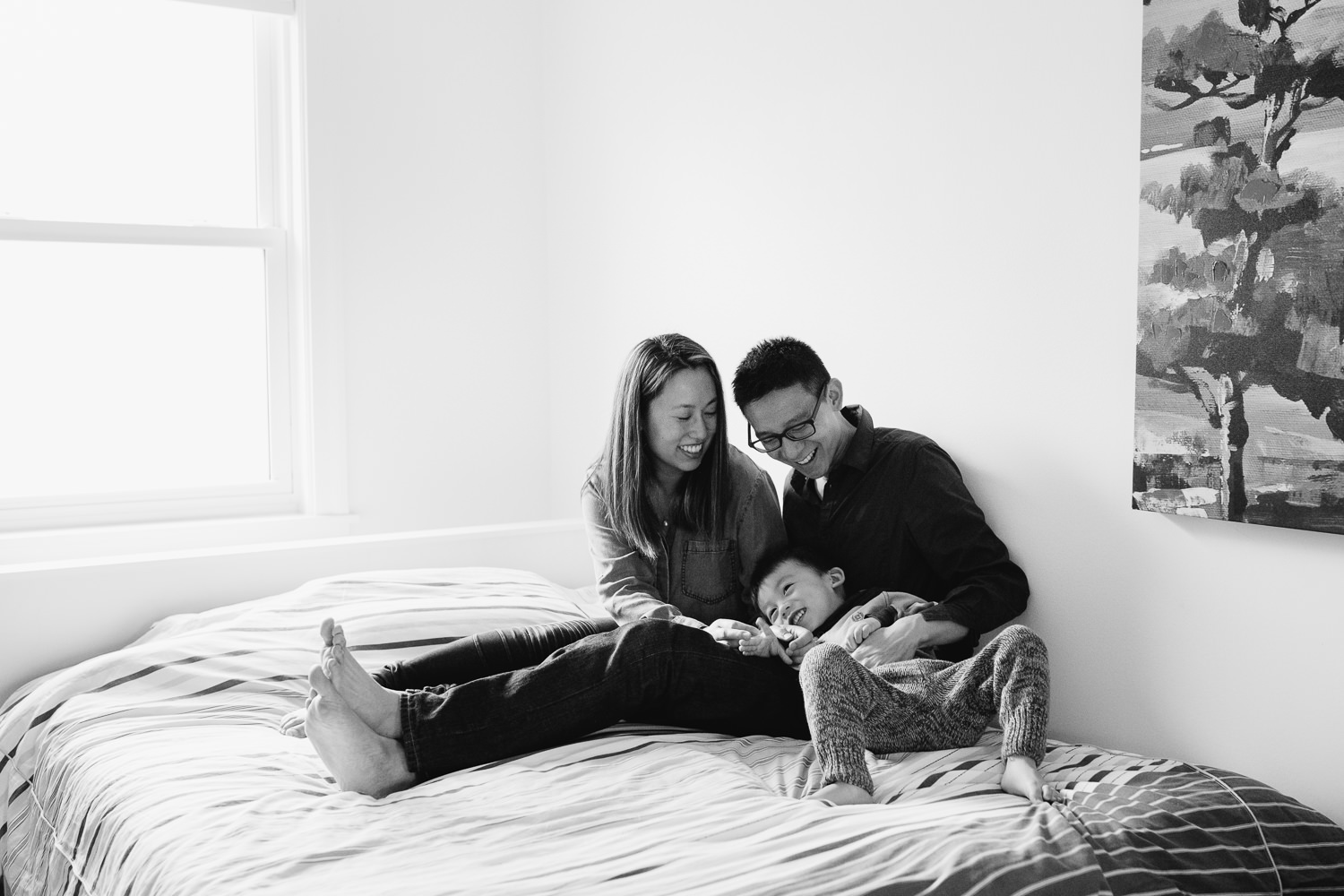 mom and dad sitting on bed ticking laughing 2 year old toddler boy - Newmarket Lifestyle Photos