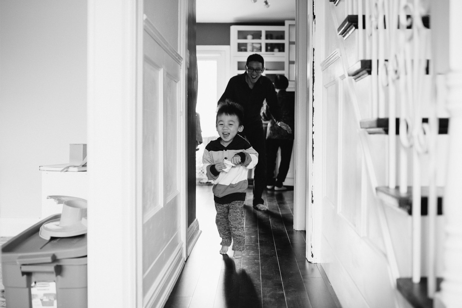 2 year old toddler boy running towards camera as dad chases behind - Stouffville Lifestyle Photography