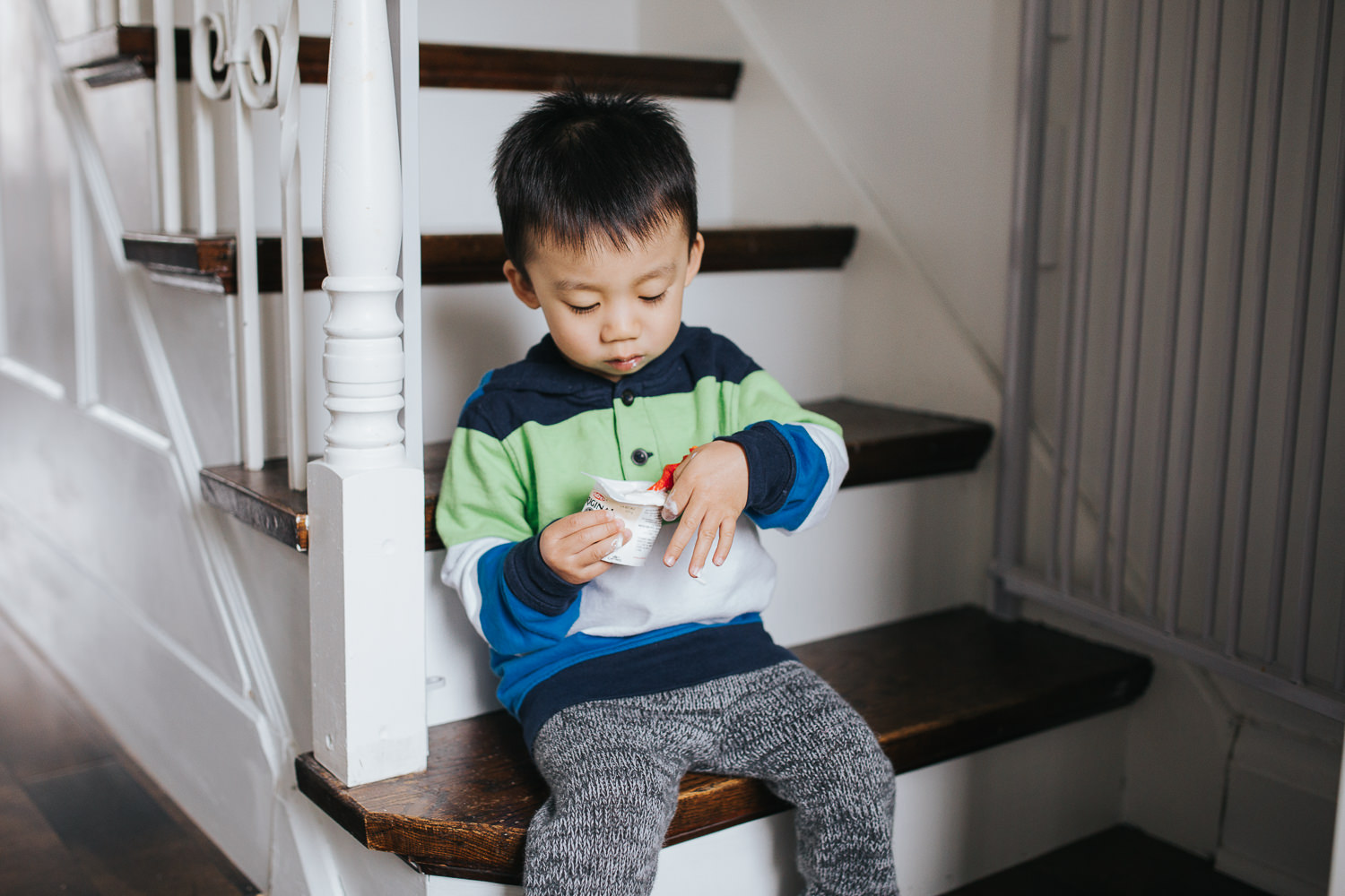 2 year old toddler boy sitting on stairs eating yogurt - Markham Lifestyle Photography