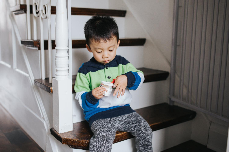 2 year old toddler boy sitting on stairs eating yogurt - Markham Lifestyle Photography