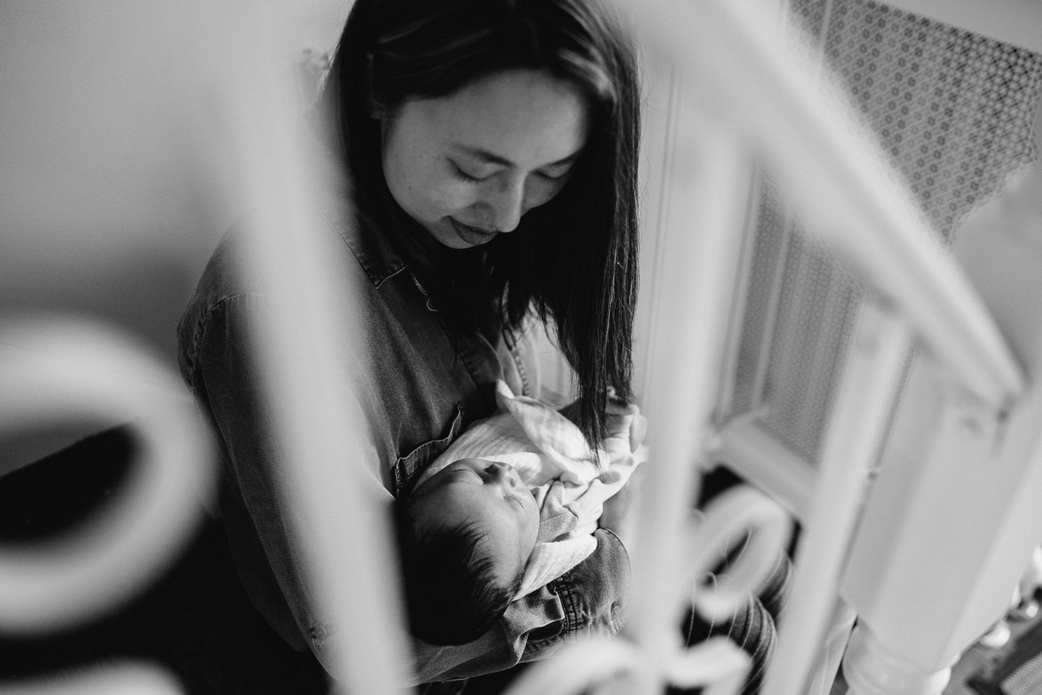 mom with dark hair sits on stairs holding 2 week old baby boy - Newmarket In-Home Photography