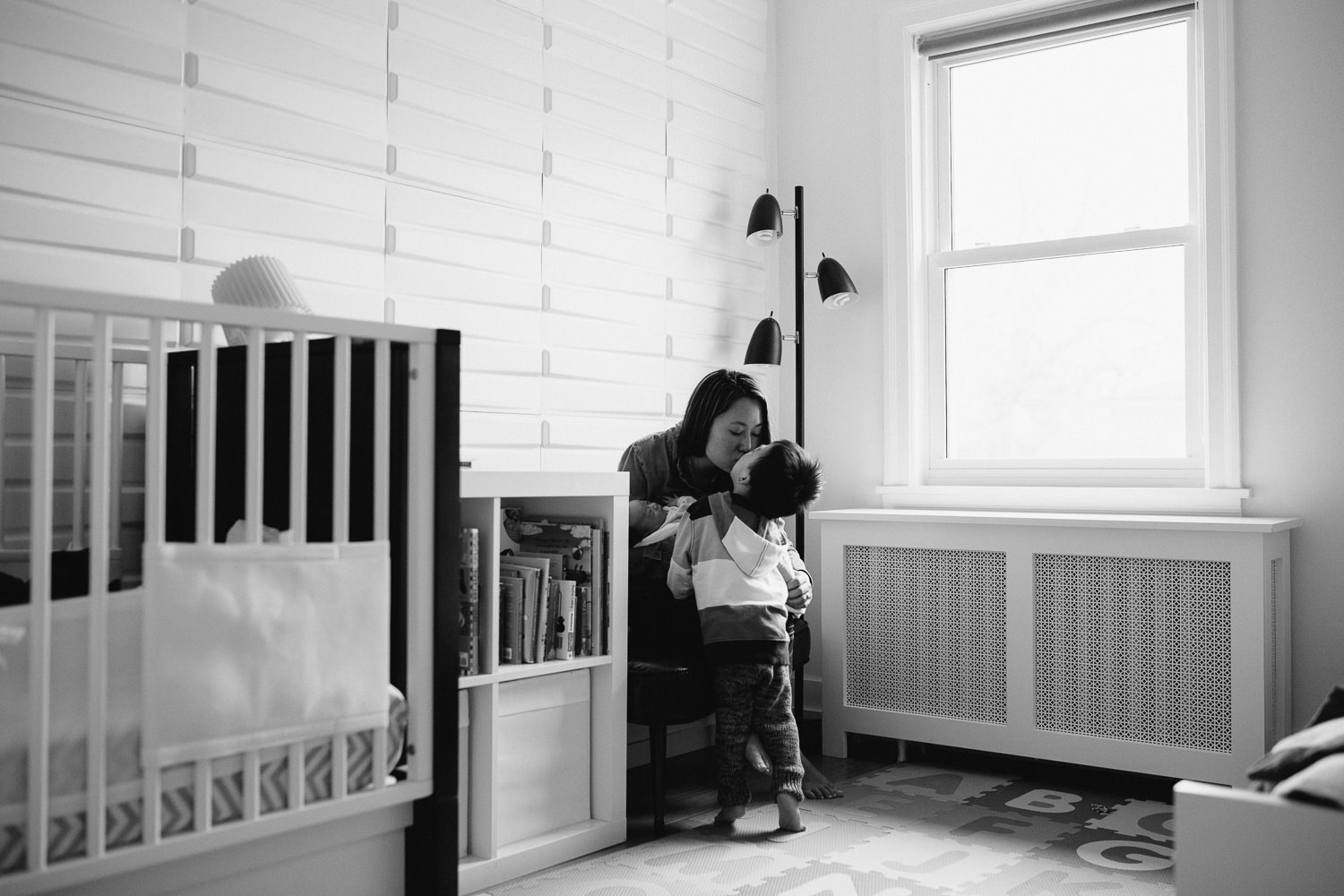 2 year old toddler boy kisses mom who is sitting holding 2 week old baby boy - Newmarket In-Home Photos