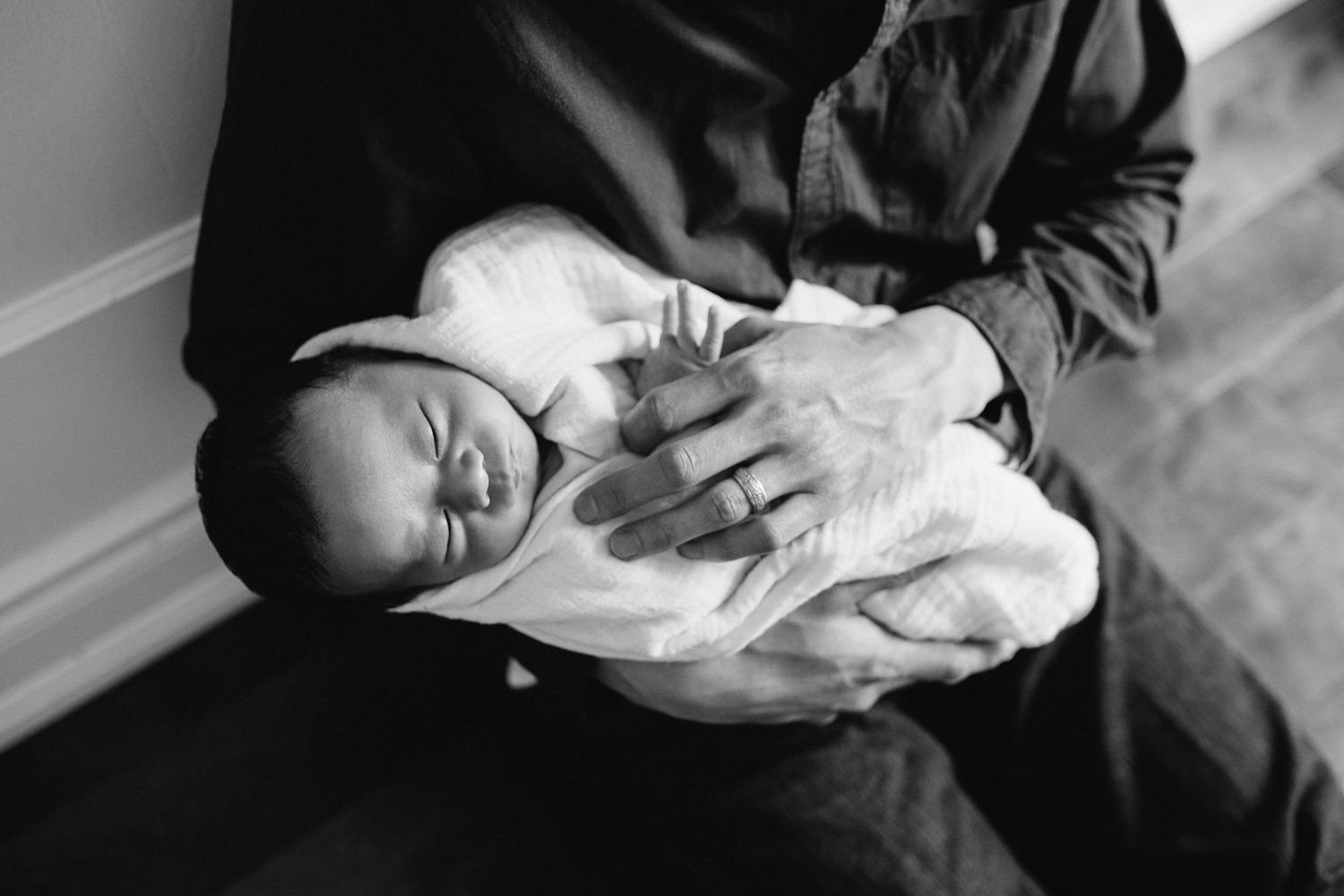 father sitting on floor holding 2 week old baby boy sleeping in white swaddle - Barrie In-Home Photos