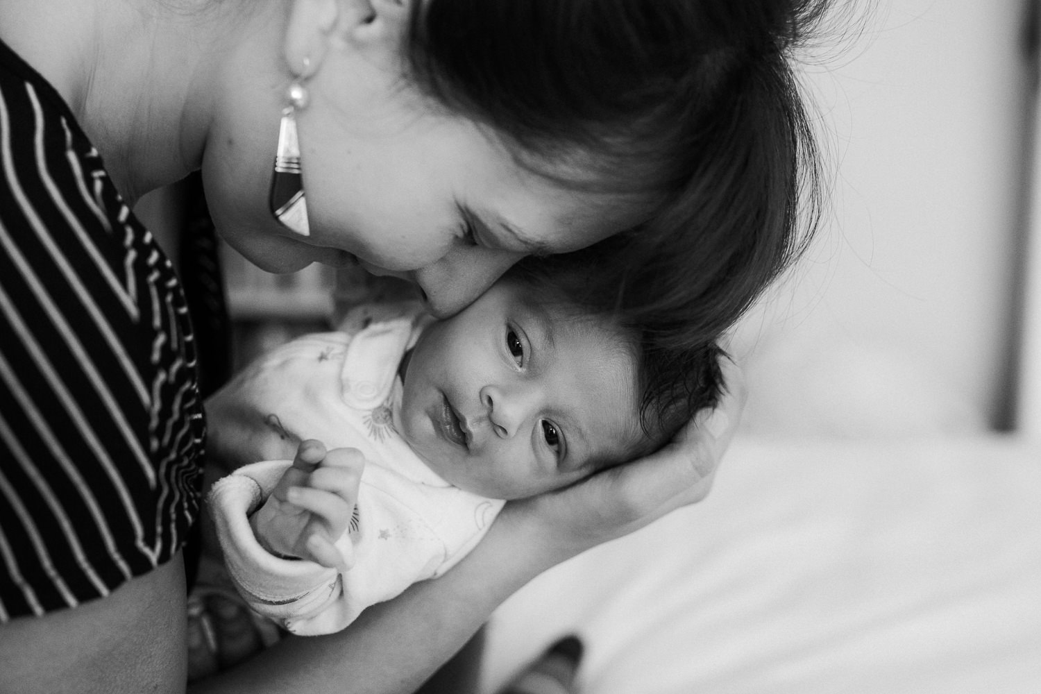 first time mom snuggling 2 week old baby daughter, face to face, baby looking at camera - Newmarket Lifestyle Photography
