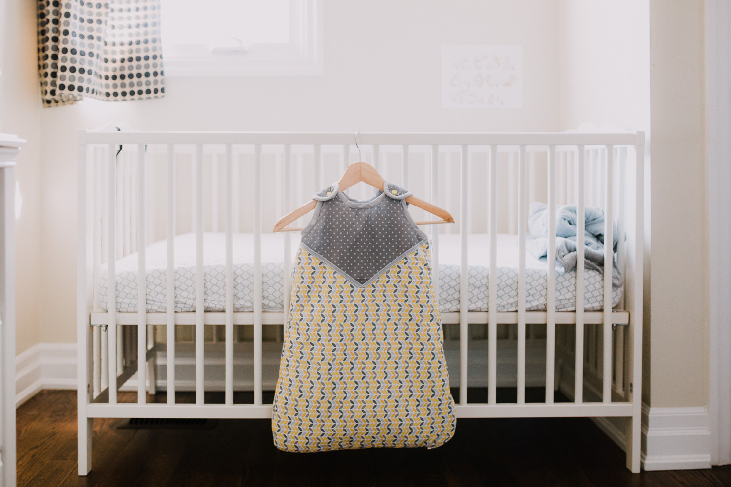 handmade yellow and grey sleep sack hanging on crib in nursery - Markham Lifestyle Photography