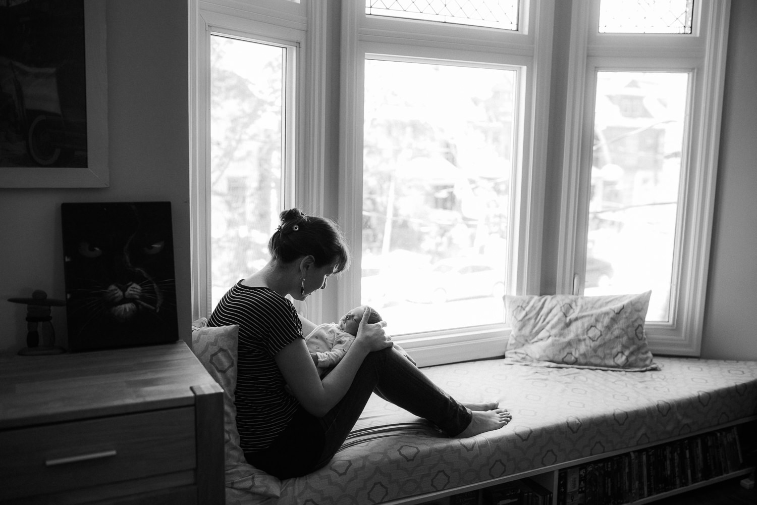 new mom sitting on window seat holding 2 week old baby girl - Newmarket Lifestyle Photography