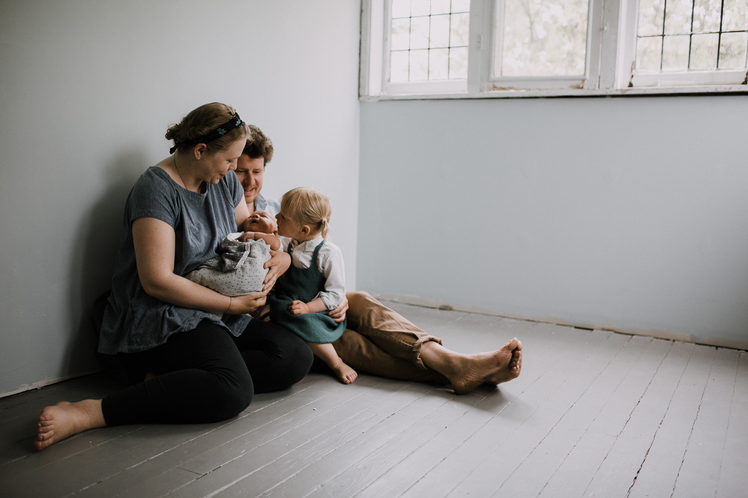 family of four sitting on floor, toddler sister looking at baby brother in mom's arms - Newmarket Lifestyle Family Photography