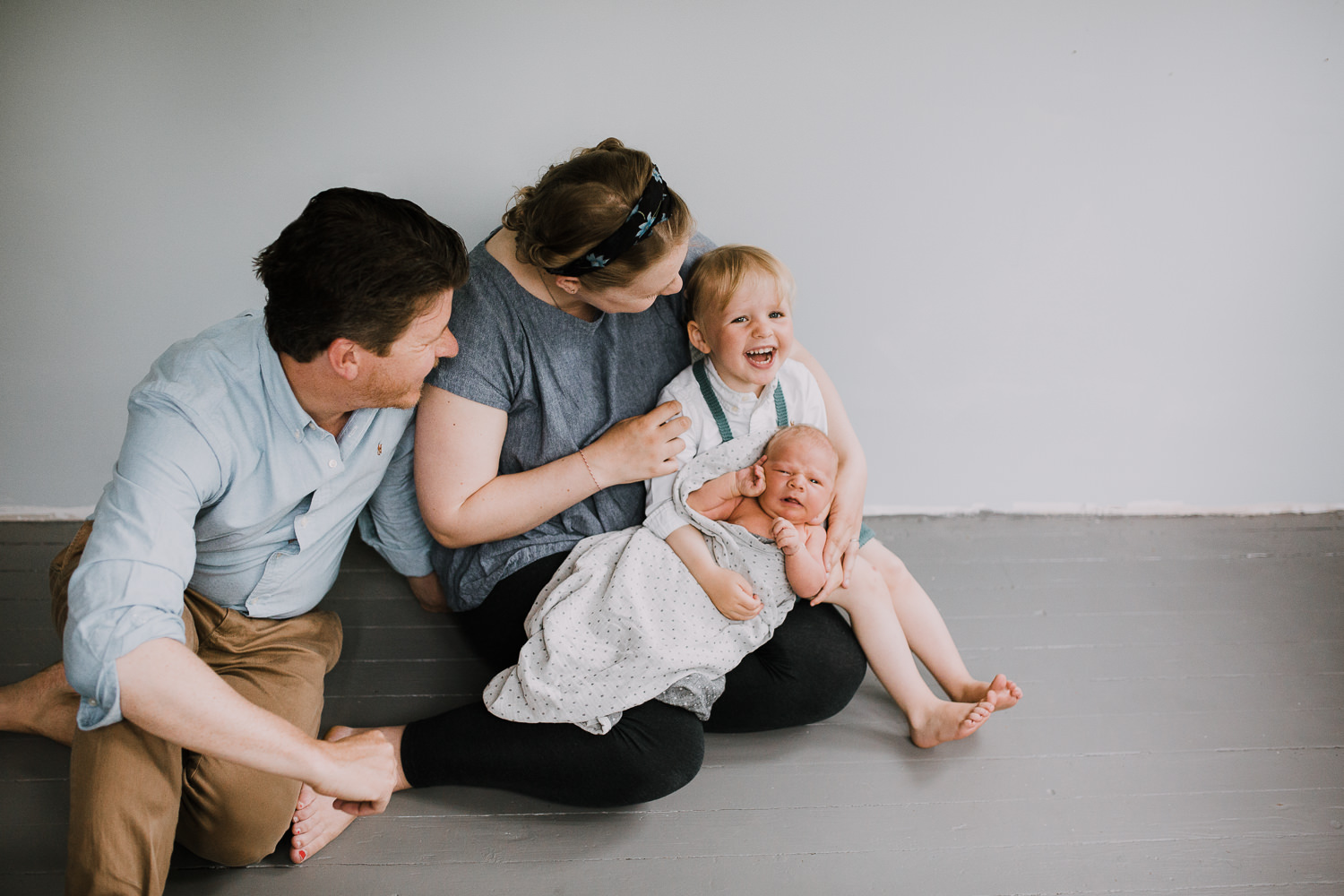 family of four sitting on ground, 2 year old toddler girl holds 10 day old baby boy - Markham Lifestyle Family Photography