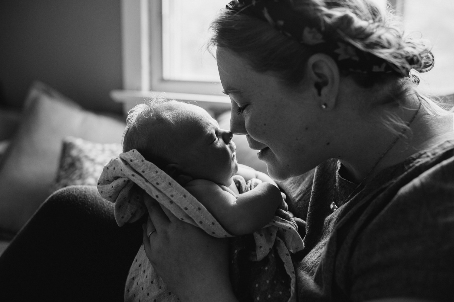 mom sits on couch with 10 day old baby boy, nose-to-nose - Barrie In-Home Family Photos