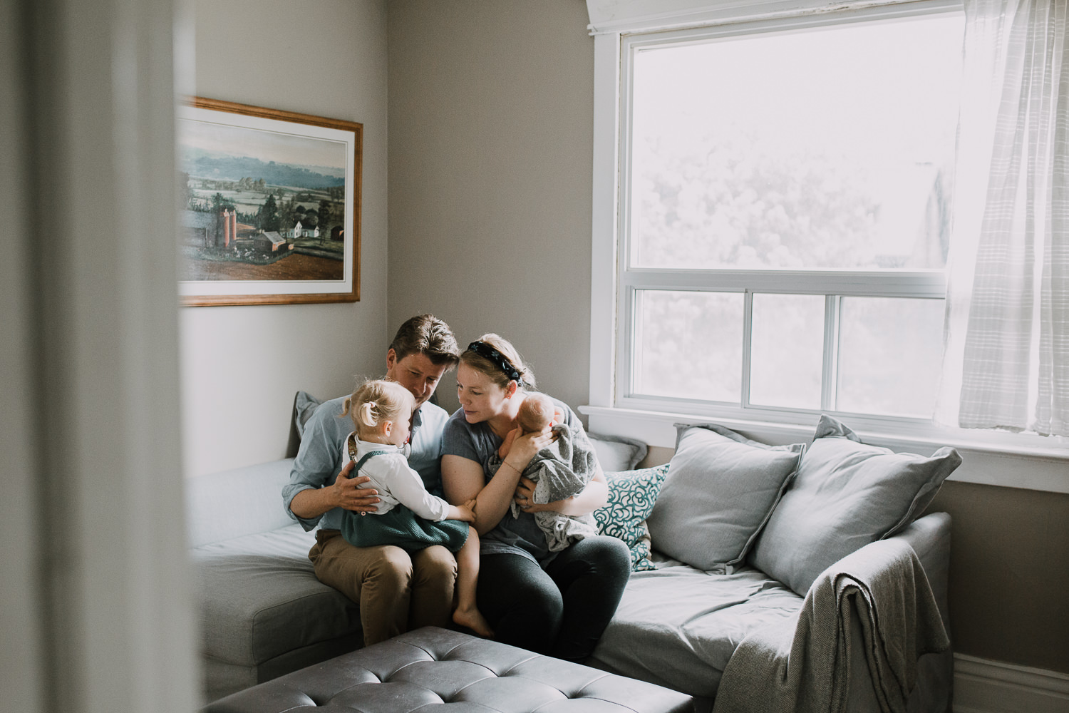 family of four with 2 year old toddler girl and 10 day old baby boy sitting on couch together - Stouffville Lifestyle Family Photos