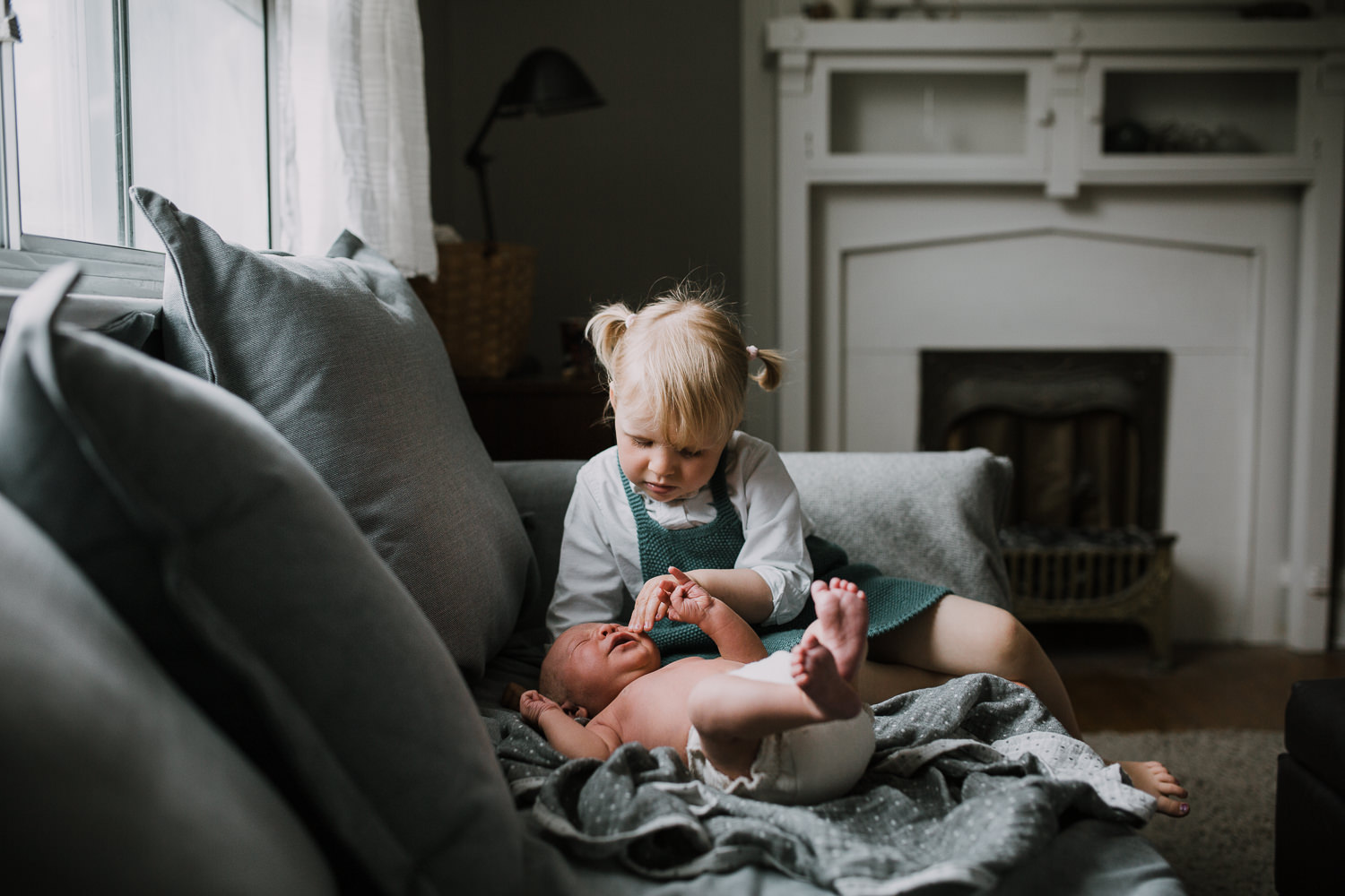 2 year old toddler girl sitting on couch looking at and soothing 10 day old baby brother - Newmarket In-Home Family Photos