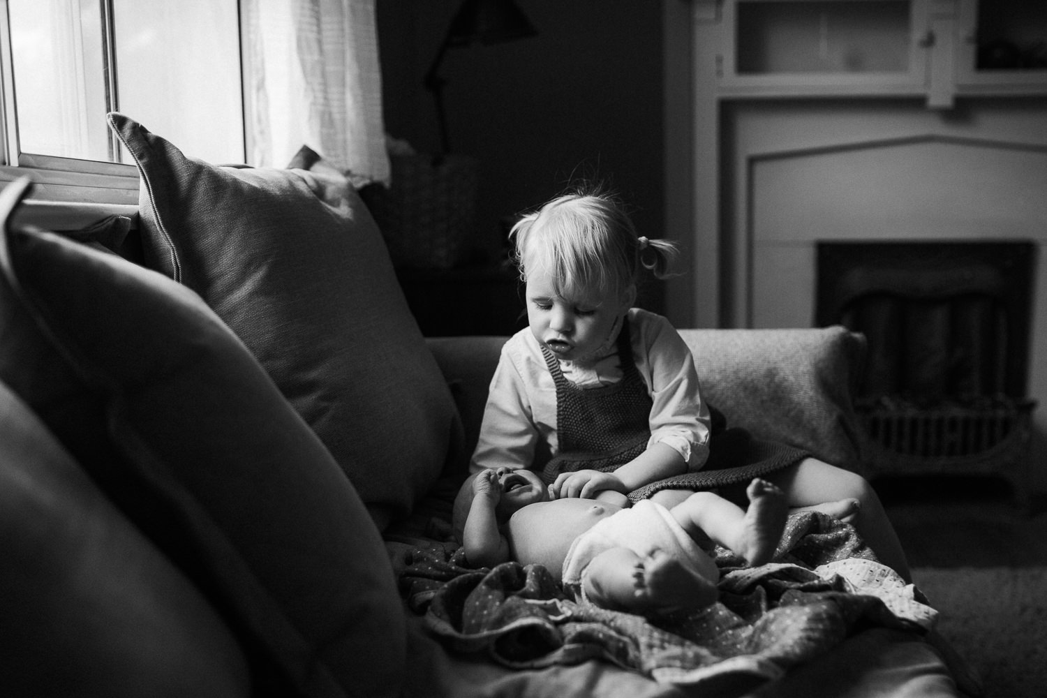 2 year old toddler girl sitting on couch looking at and soothing 10 day old baby brother - Stouffville In-Home Family Photos